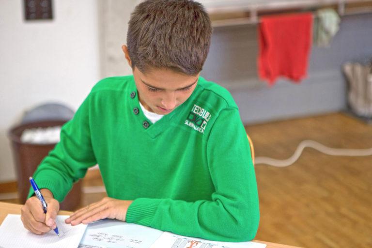 Schüler löst Aufgaben im Heft