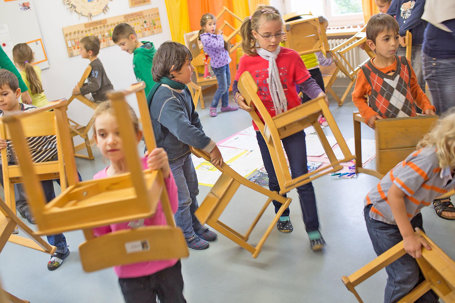 Kinder im Kindergarten räumen ihre Stühle auf die Seite