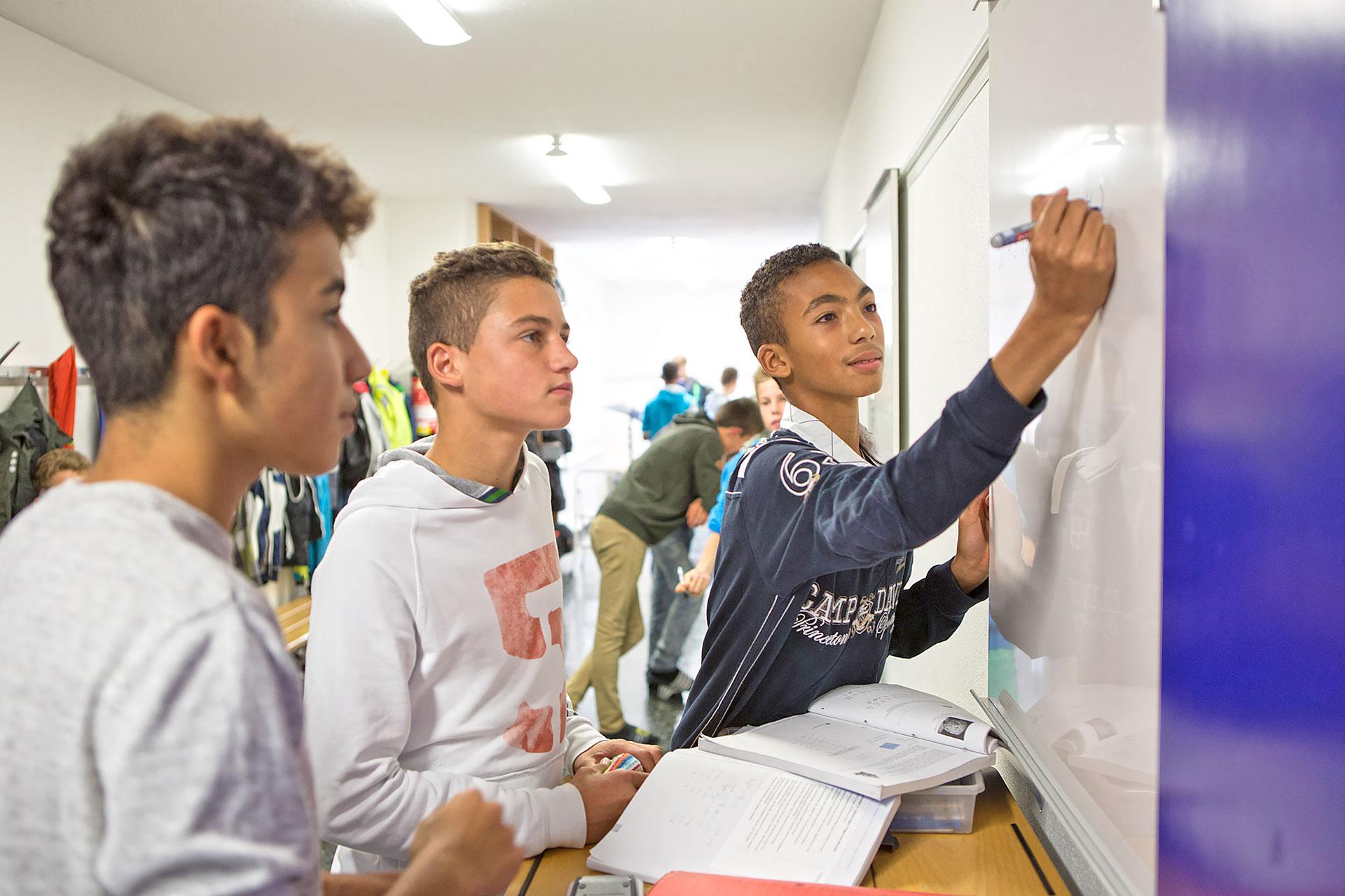 drei Schüler lösen Aufgaben an einem Whiteboard