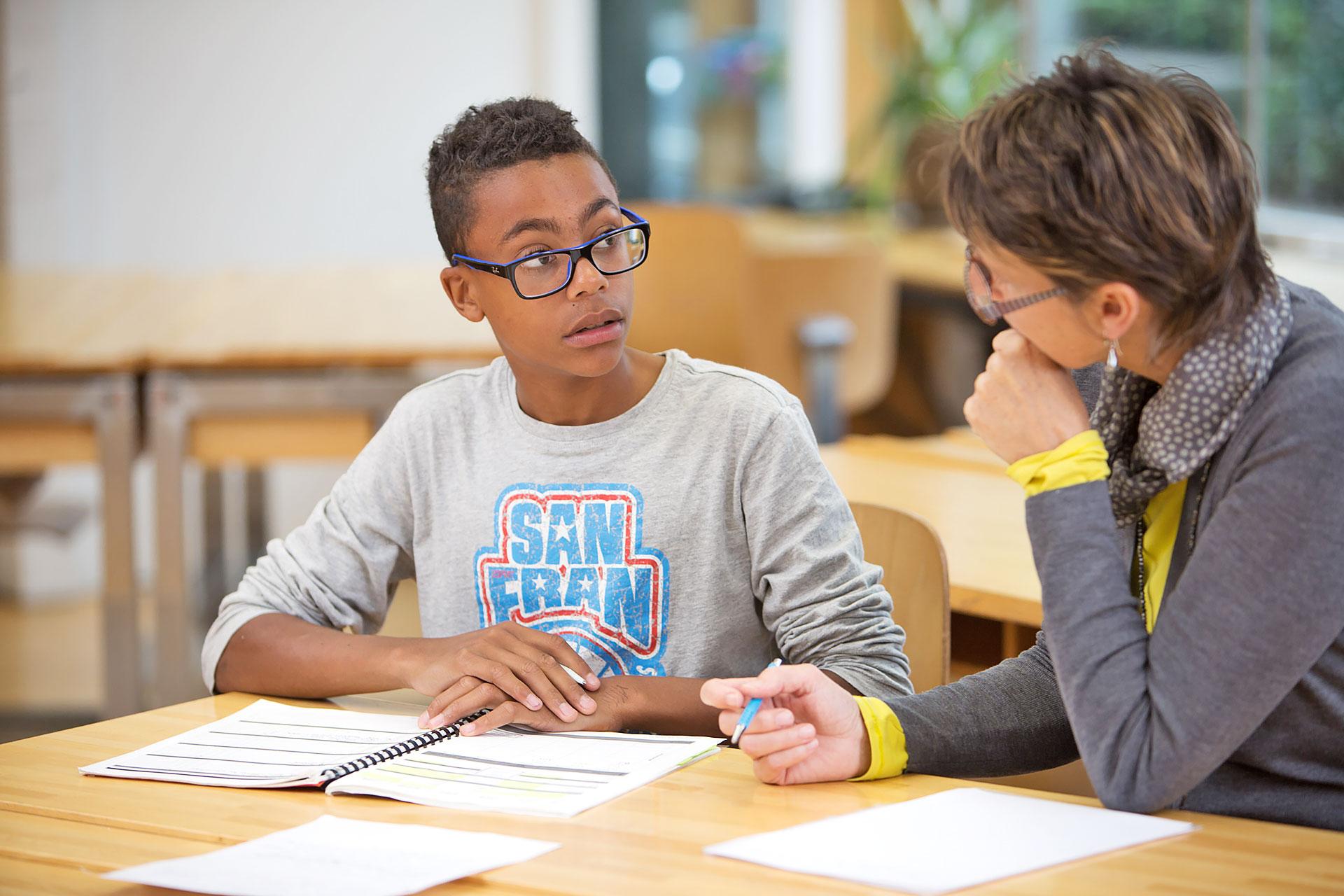 Lehrerin bespricht mit Schüler seine Leistungsbeurteilung