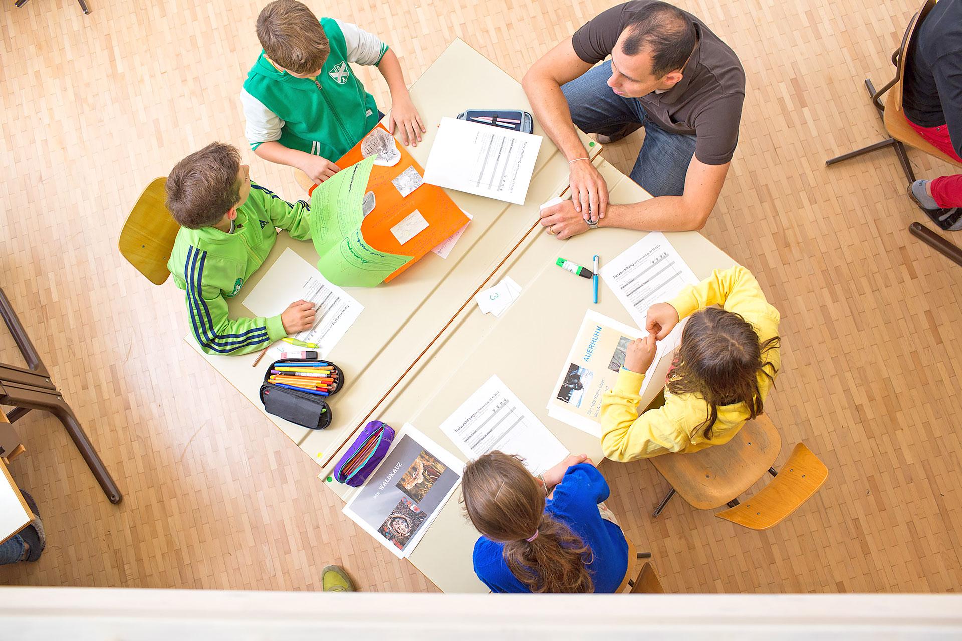 Lehrer bespricht mit vier Schülern/-innen am Gruppentisch die Tiervorstellungen