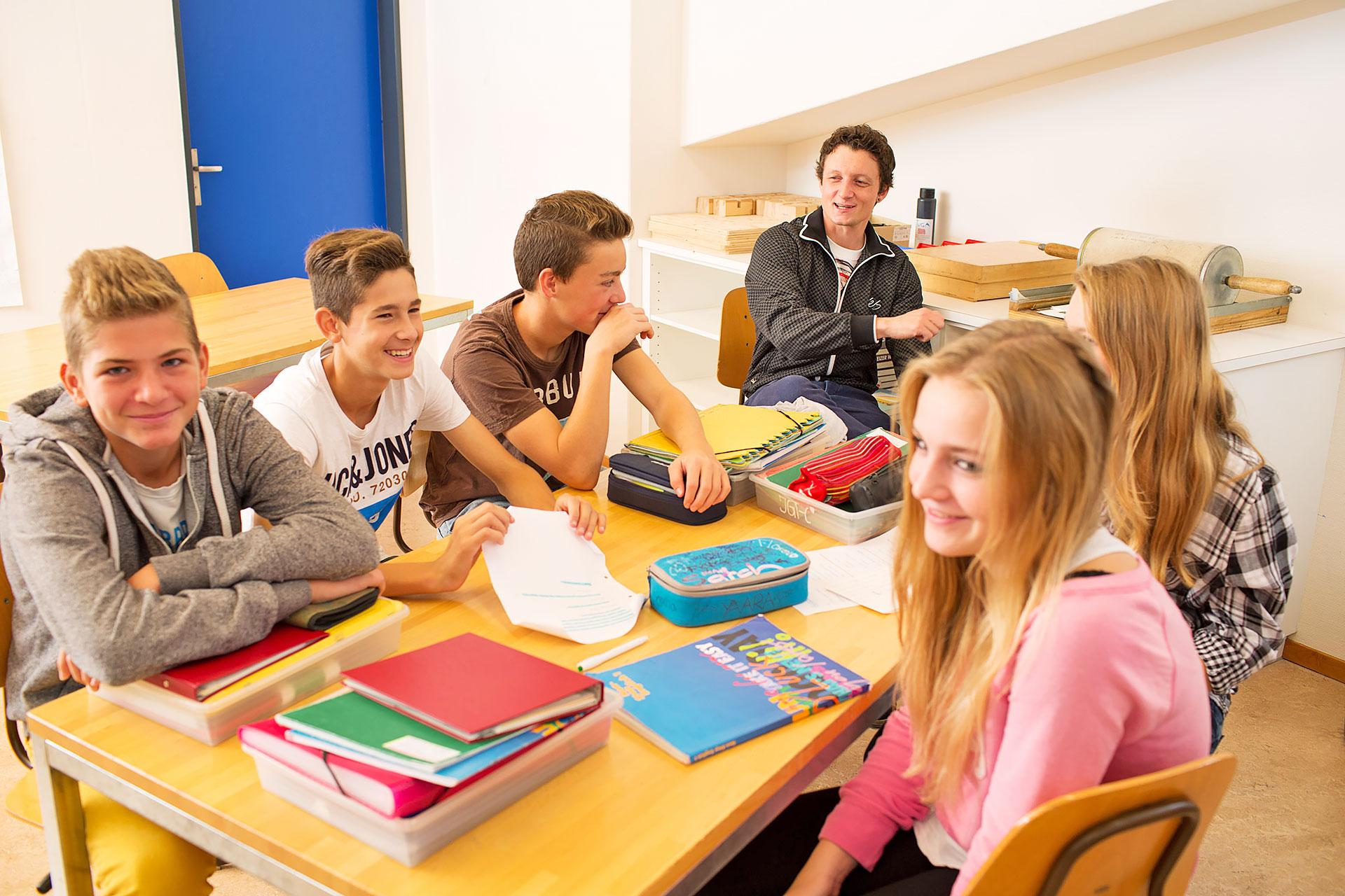 Schüler sitzen lachend am Gruppentisch