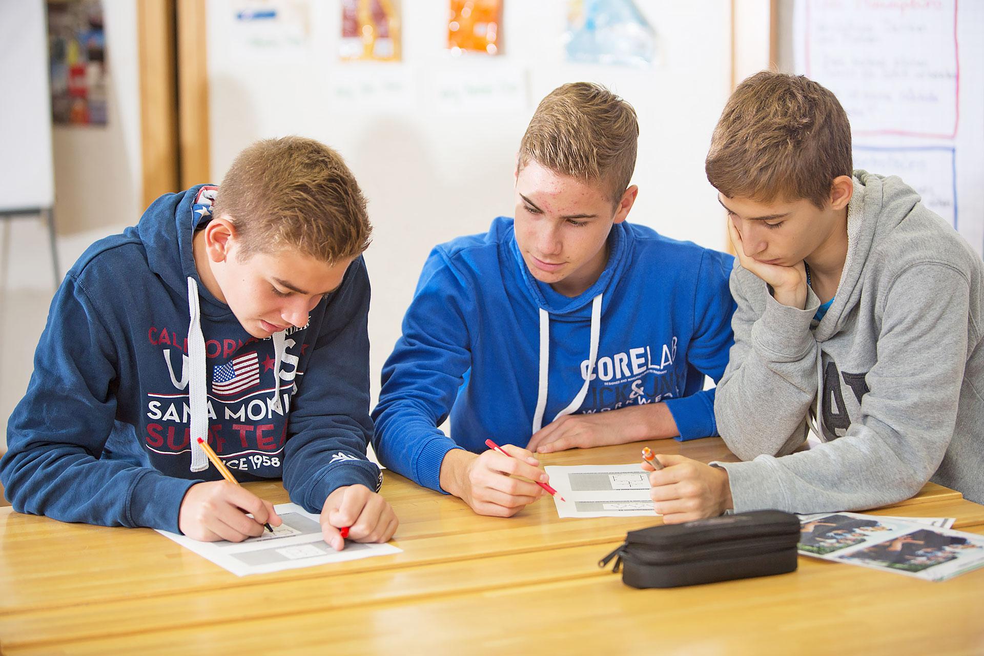Drei Schüler bearbeiten kooperativ eine Aufgabe
