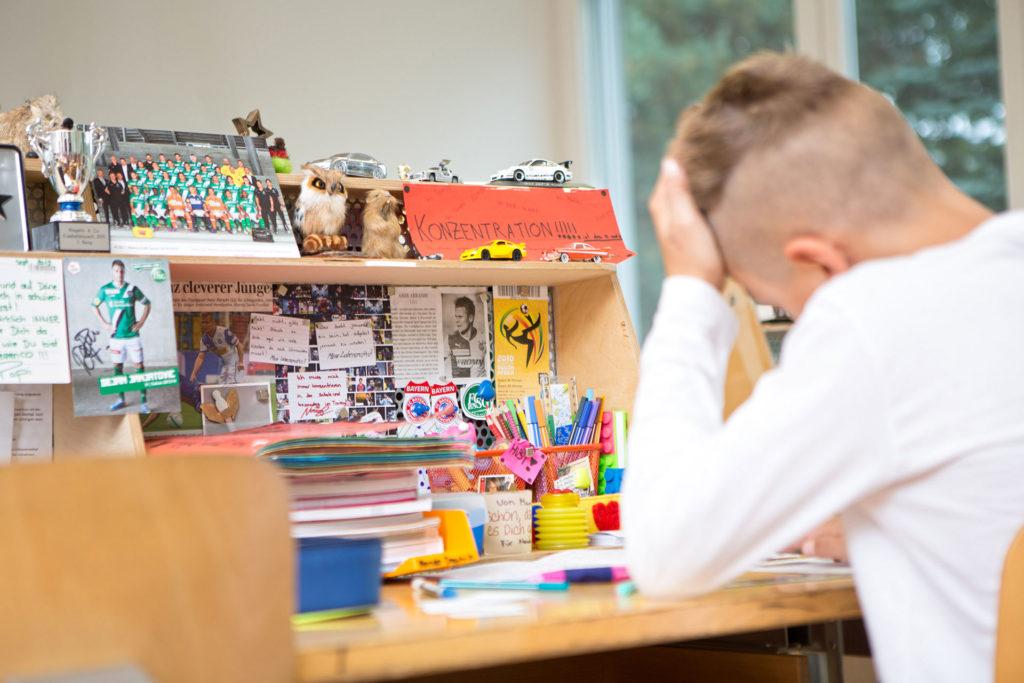 ein Schüler arbeitet an seinem persönlichen gestalteten Arbeitsplatz