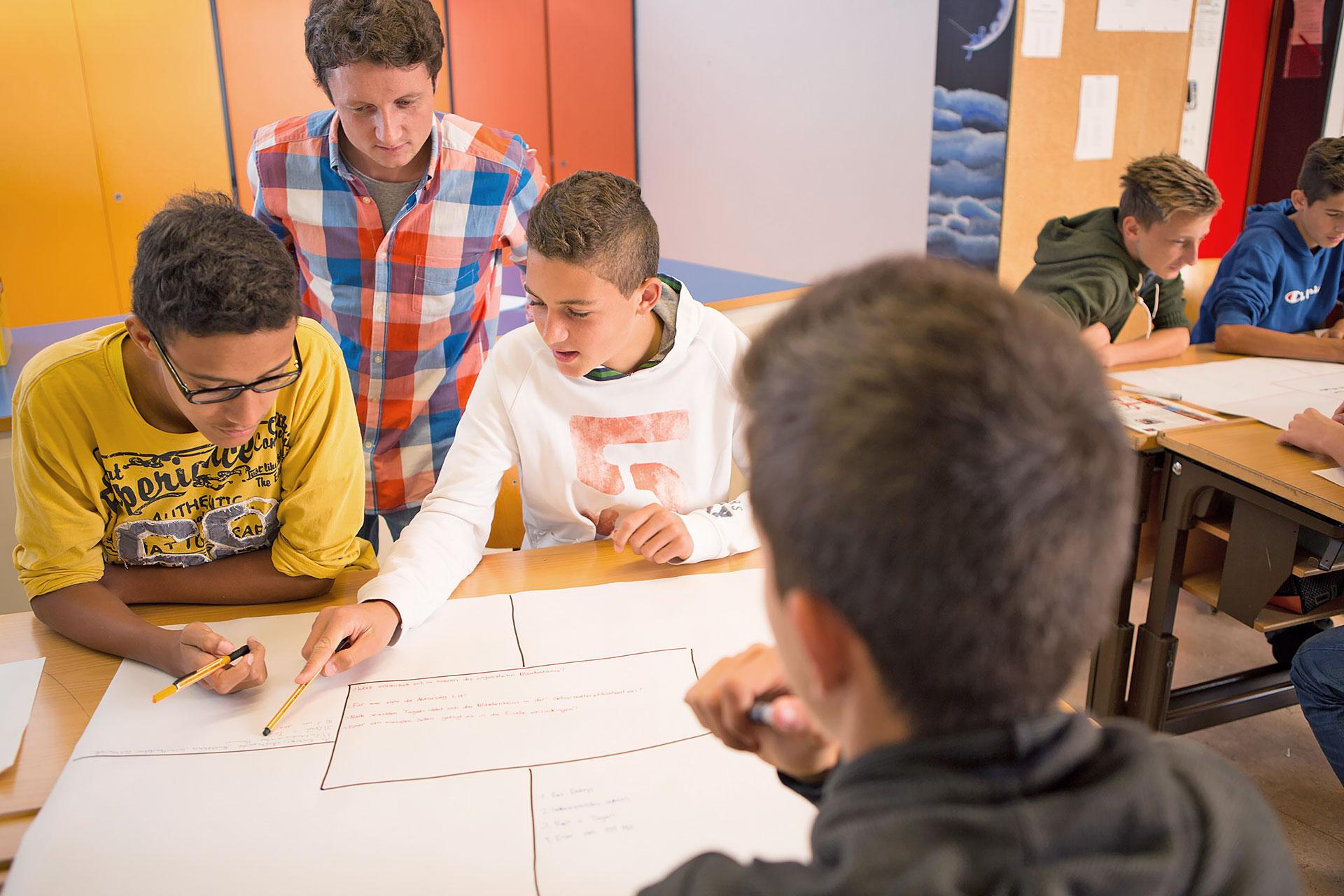 drei Schüler arbeiten an einem Placemat, Lehrer schaut dabei über die Schulter