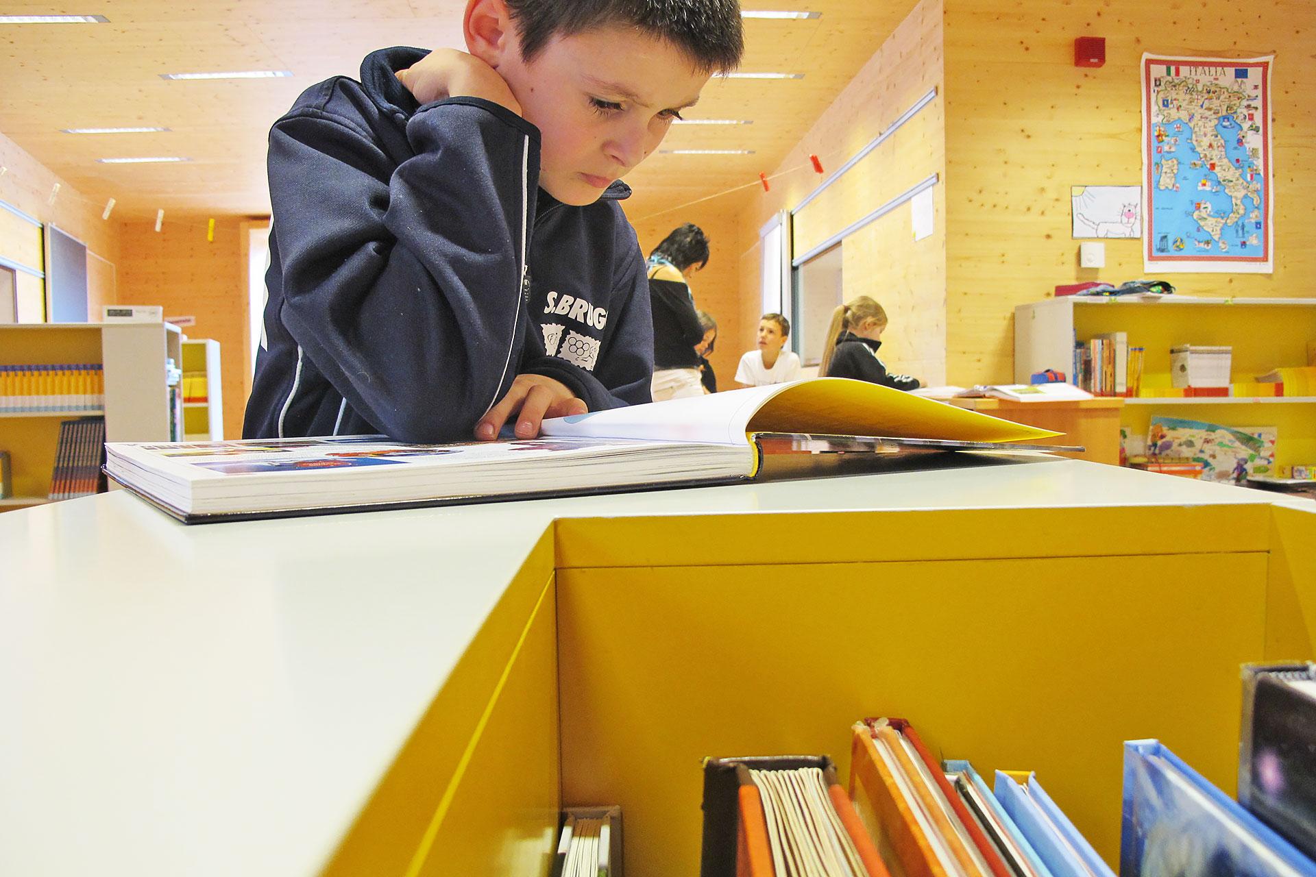 Schüler liest in einem Buch in der Bibliotheksecke des Schulzimmers