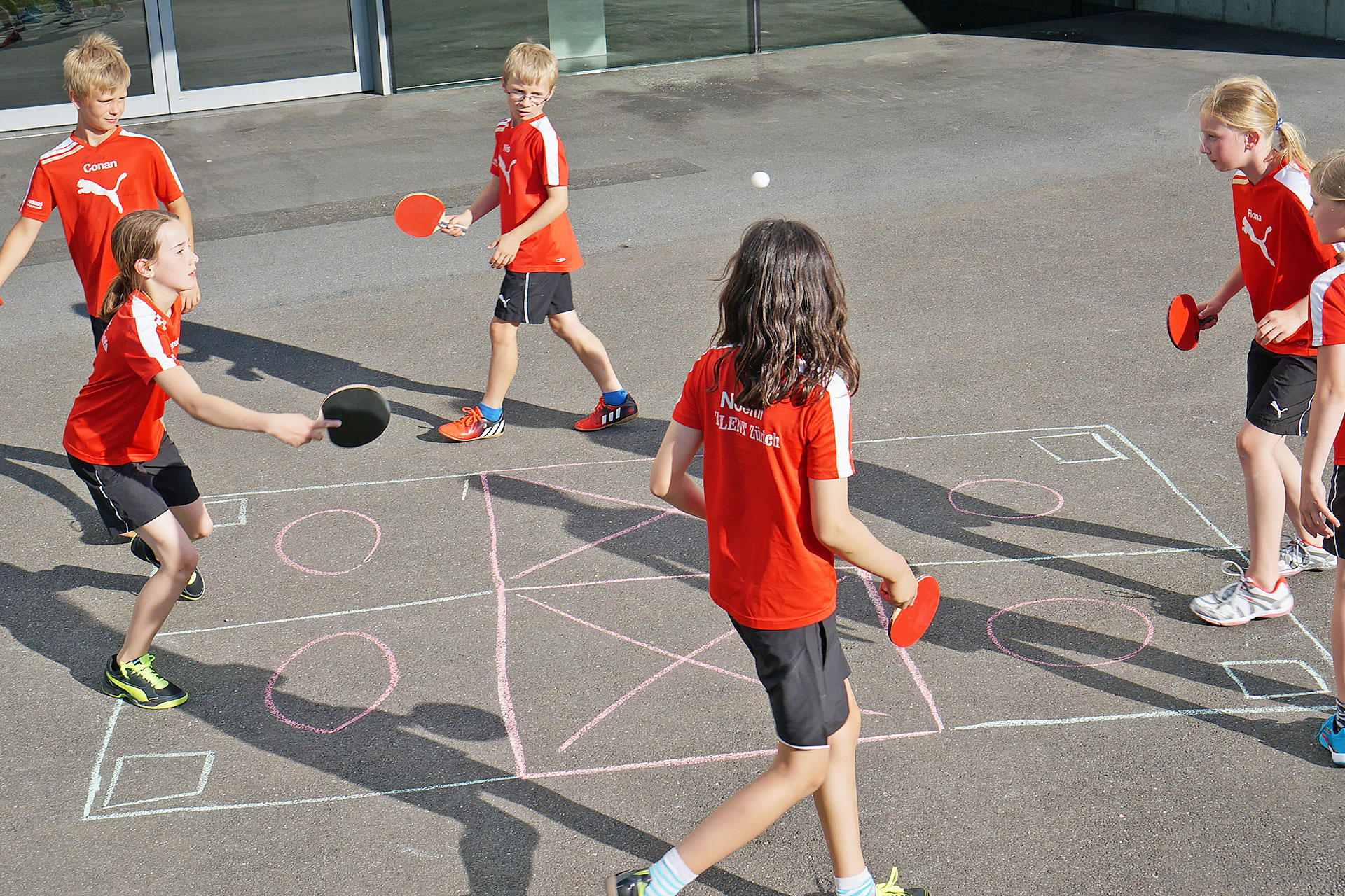sechs Schülerinnen und Schüler spielen eine Variante von Street Racket mit Tischtennis-Schlägern und - Ball