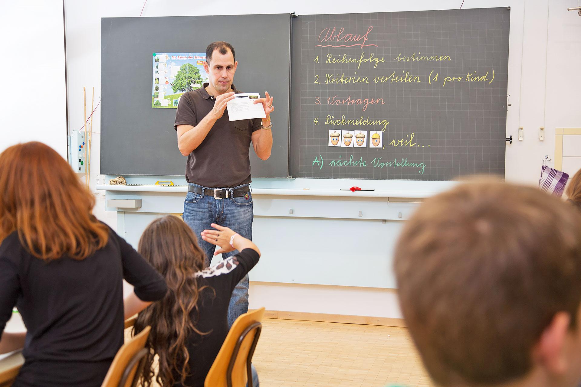 Lehrer vor Wandtafel mit Ablauf für Tiervorstellungsrunde