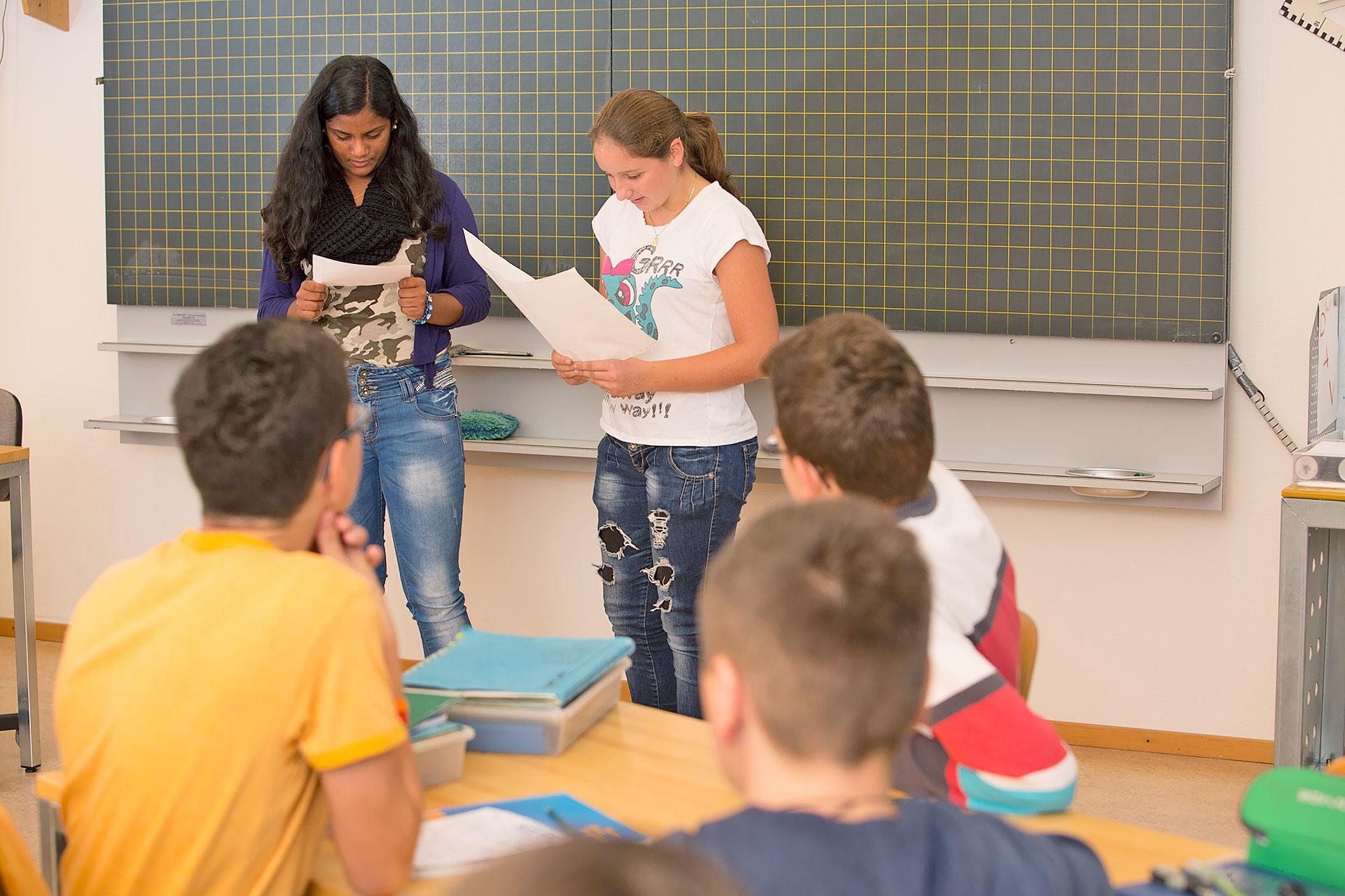 zwei Schülerinnen halten einen Vortrag