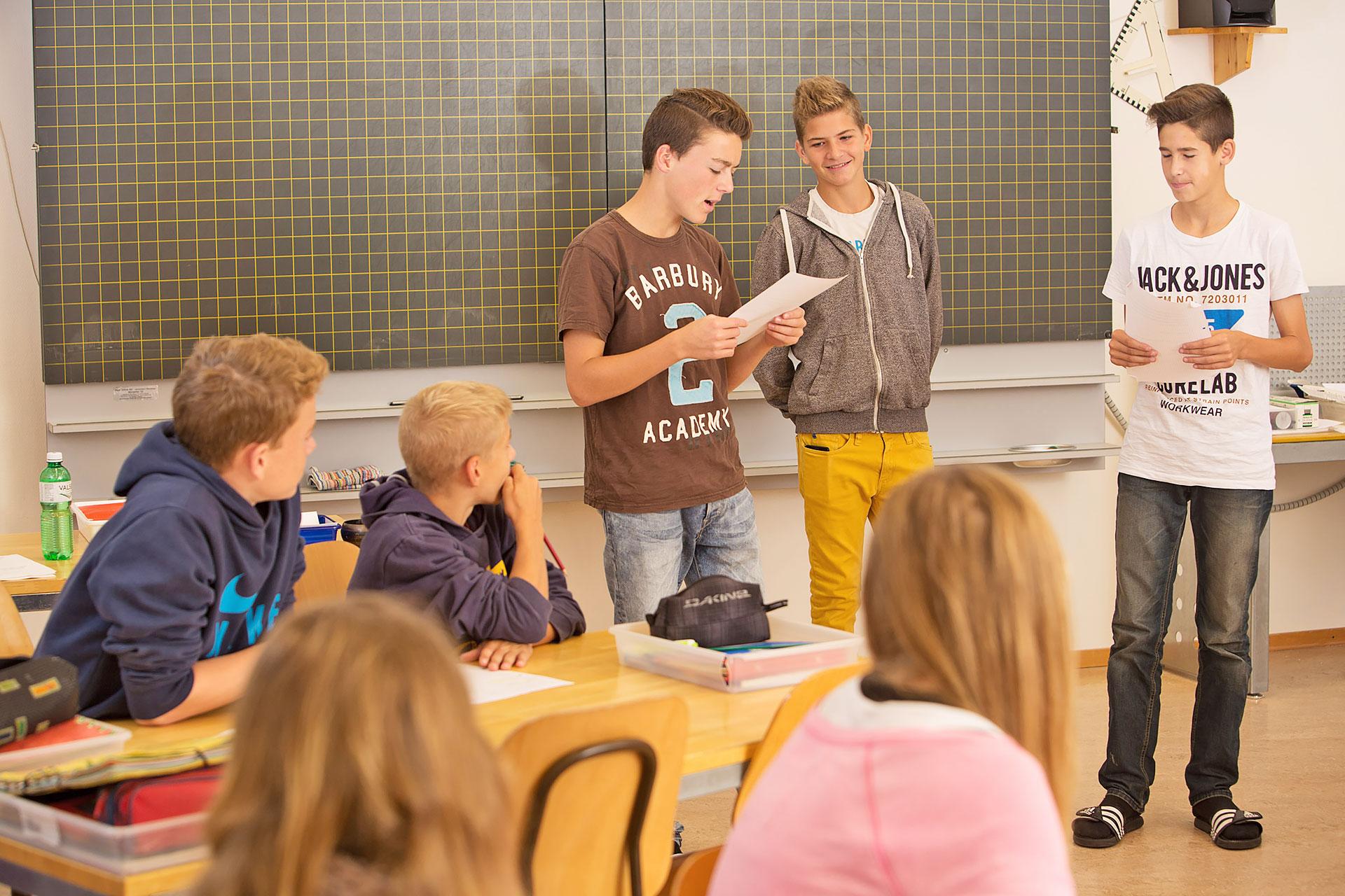 drei Schüler halten einen Vortag vor der Klasse