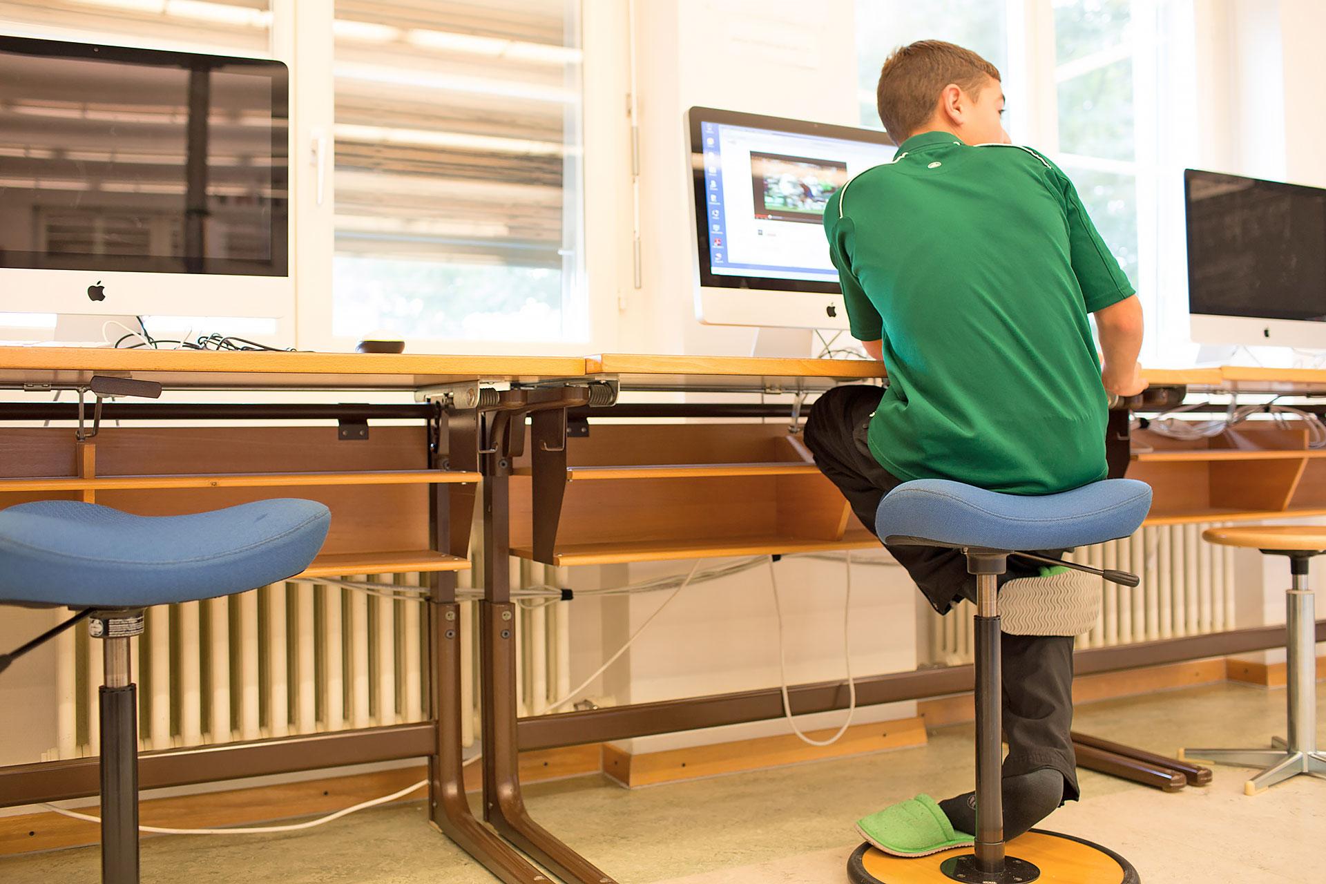 ein Schüler sitzt vor einem Computer im Schulzimmer