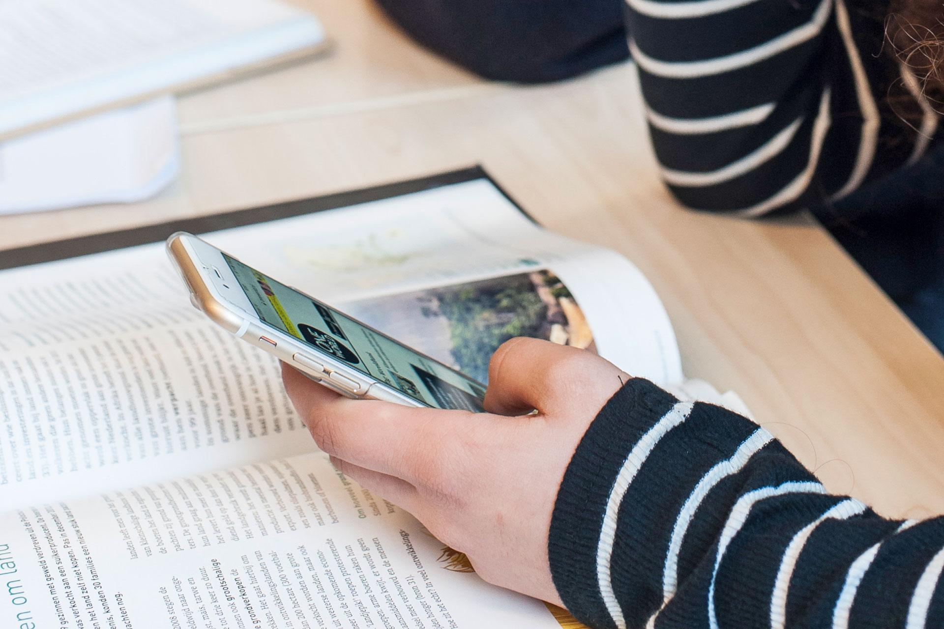Schülerin schlägt etwas auf dem Smartphone nach