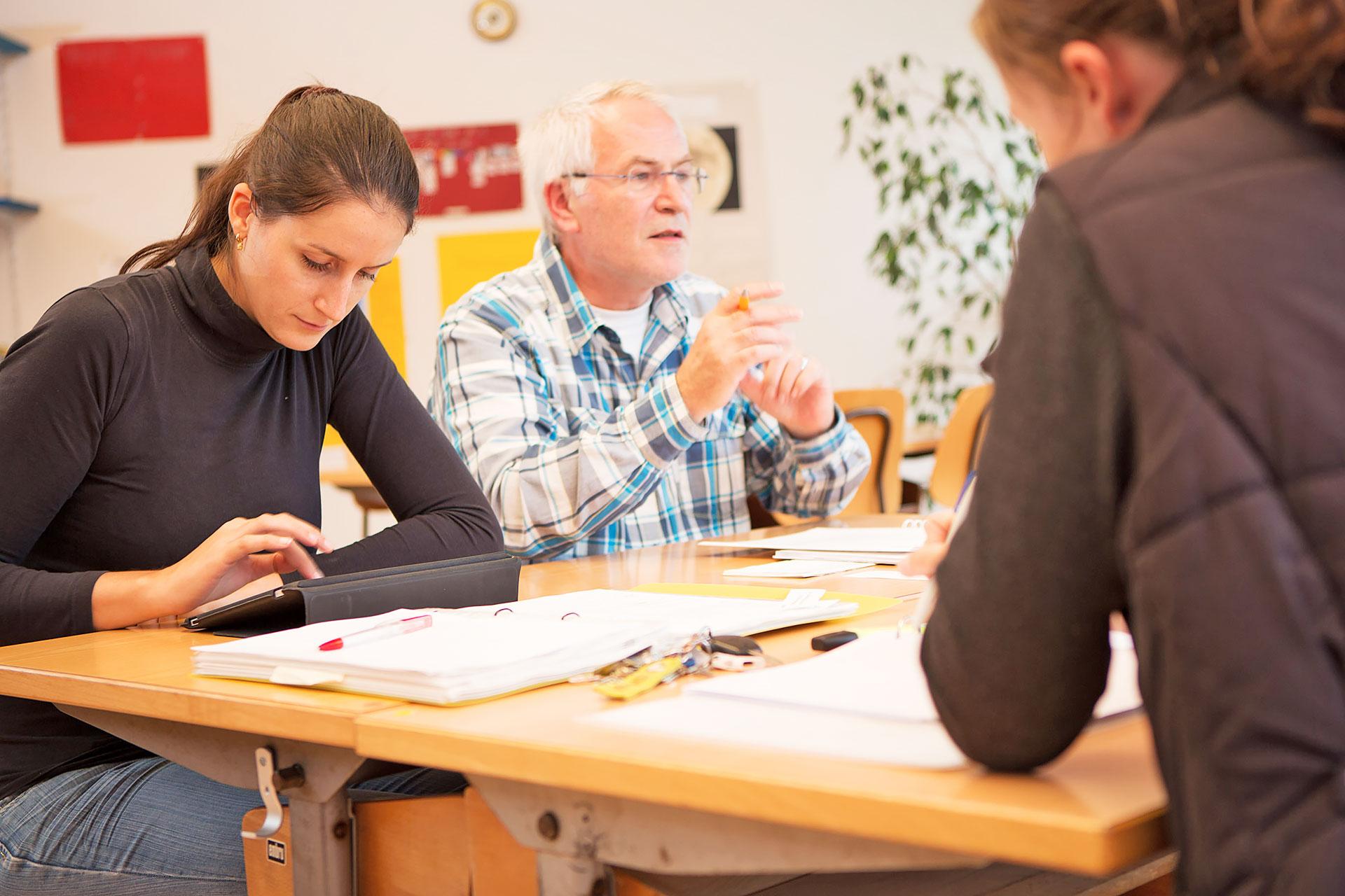 eine Lehrerin macht sich während der Teambesprechung Notizen auf ihrem Tablet