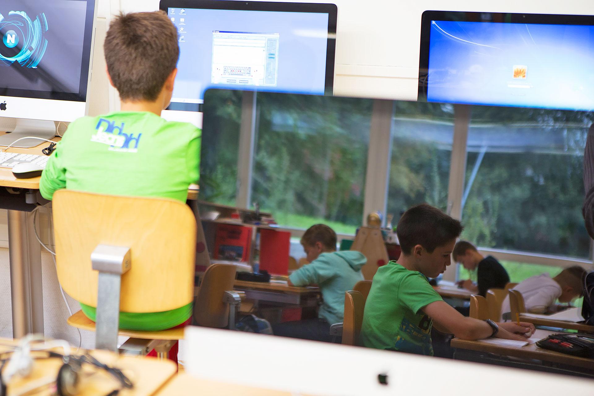 ein Schüler sitzt vor einem Computer, in einem Bildschirm spiegelt sich das Schulzimmer