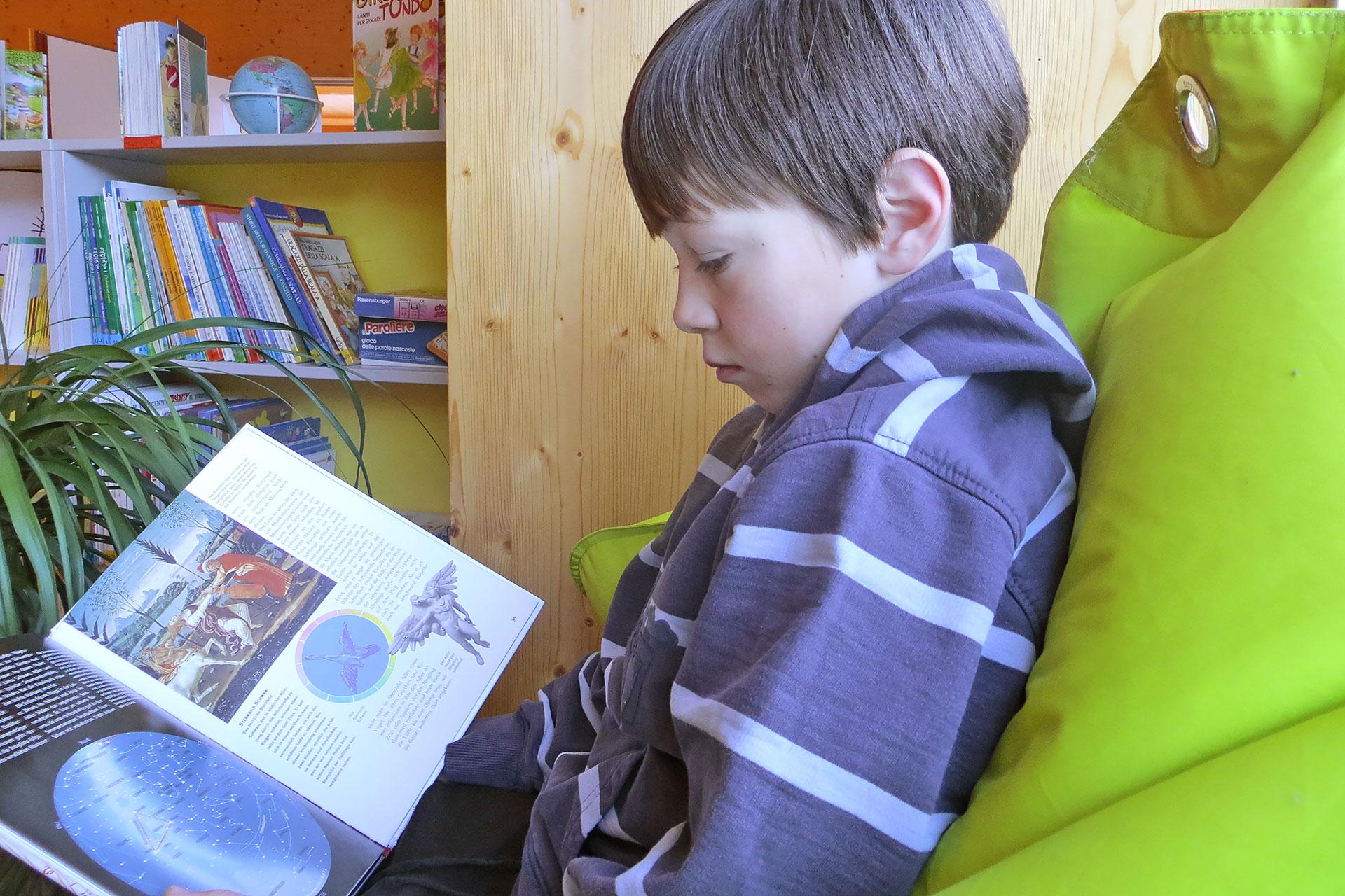 ein Schüler liest ein Buch auf einem Sitzsack