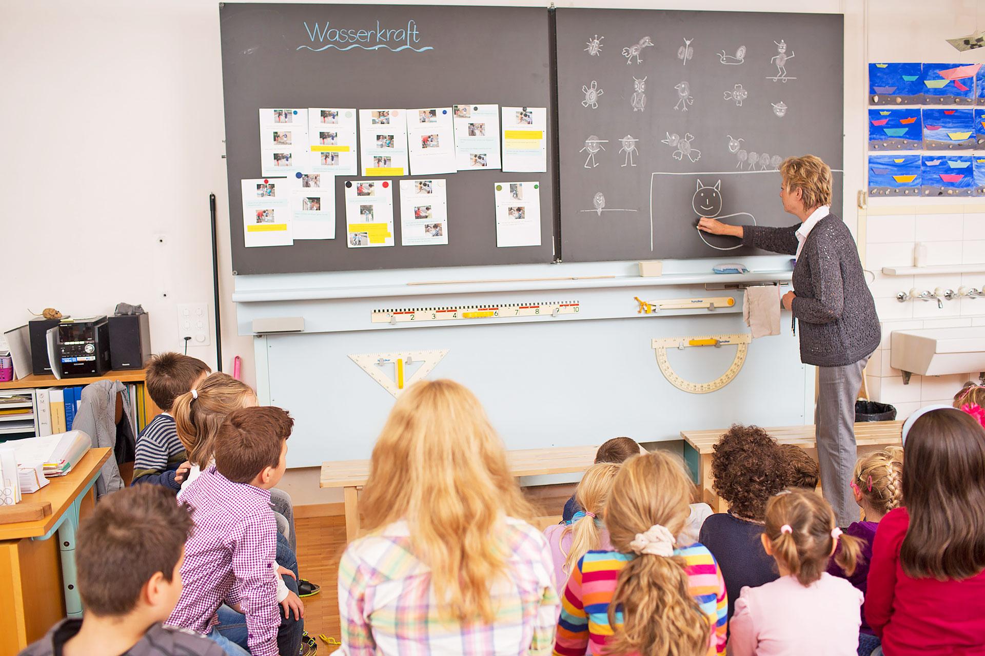 eine Lehrerin zeichnet eine einfache Katze an die Wandtafel, die Klasse schaut zu