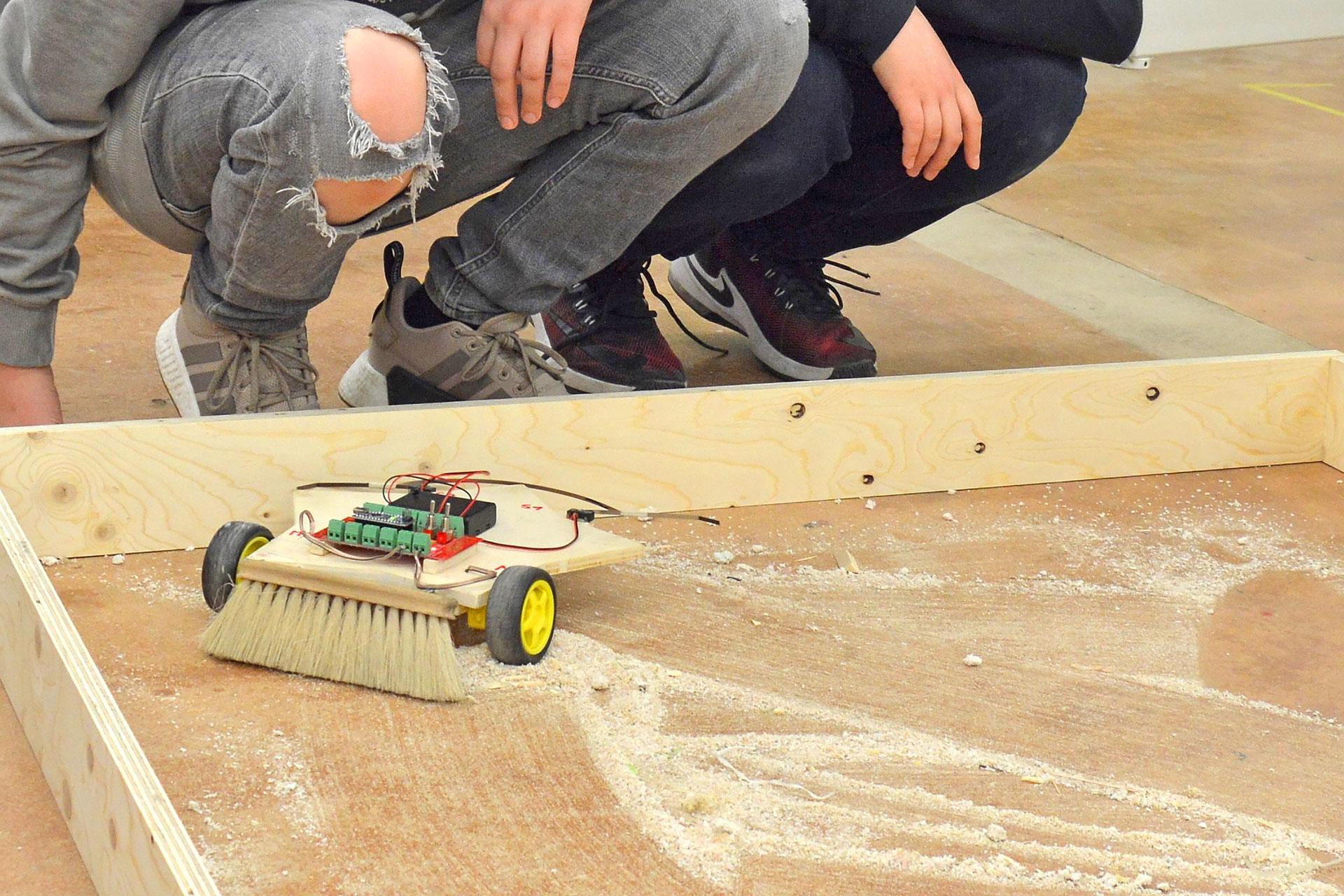 zwei Schüler testen ihren selbstfahrenden Wischroboter auf dem sägemehlbestäubten Werkstattboden