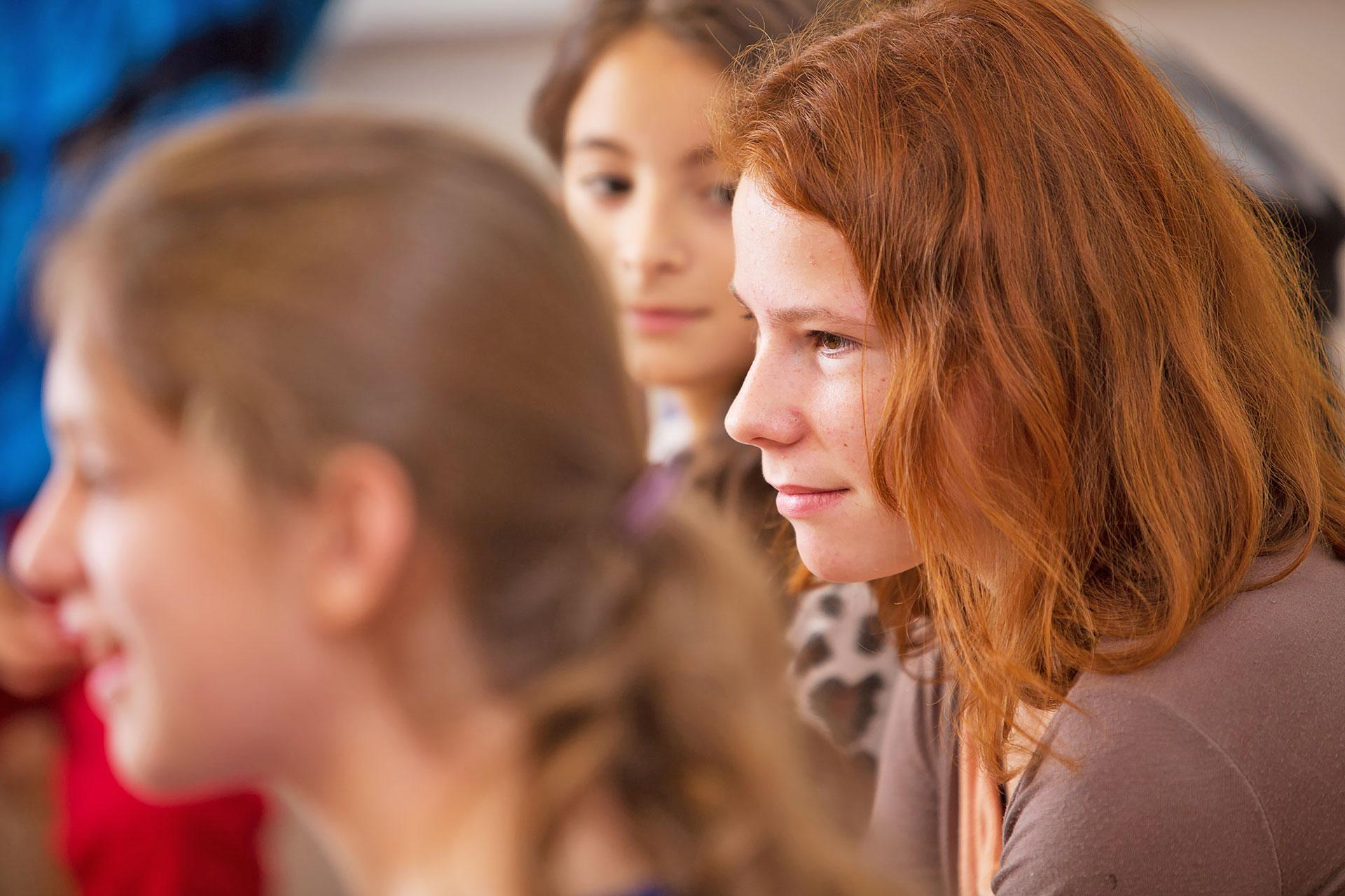 eine Schülerin hört aufmerksam zu