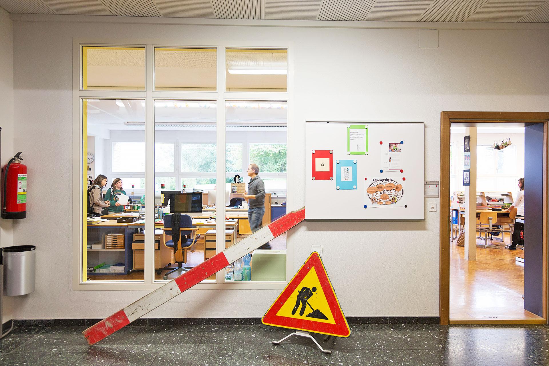 auf dem Schulkorridor steht ein Baustellen-Verkehrsschild