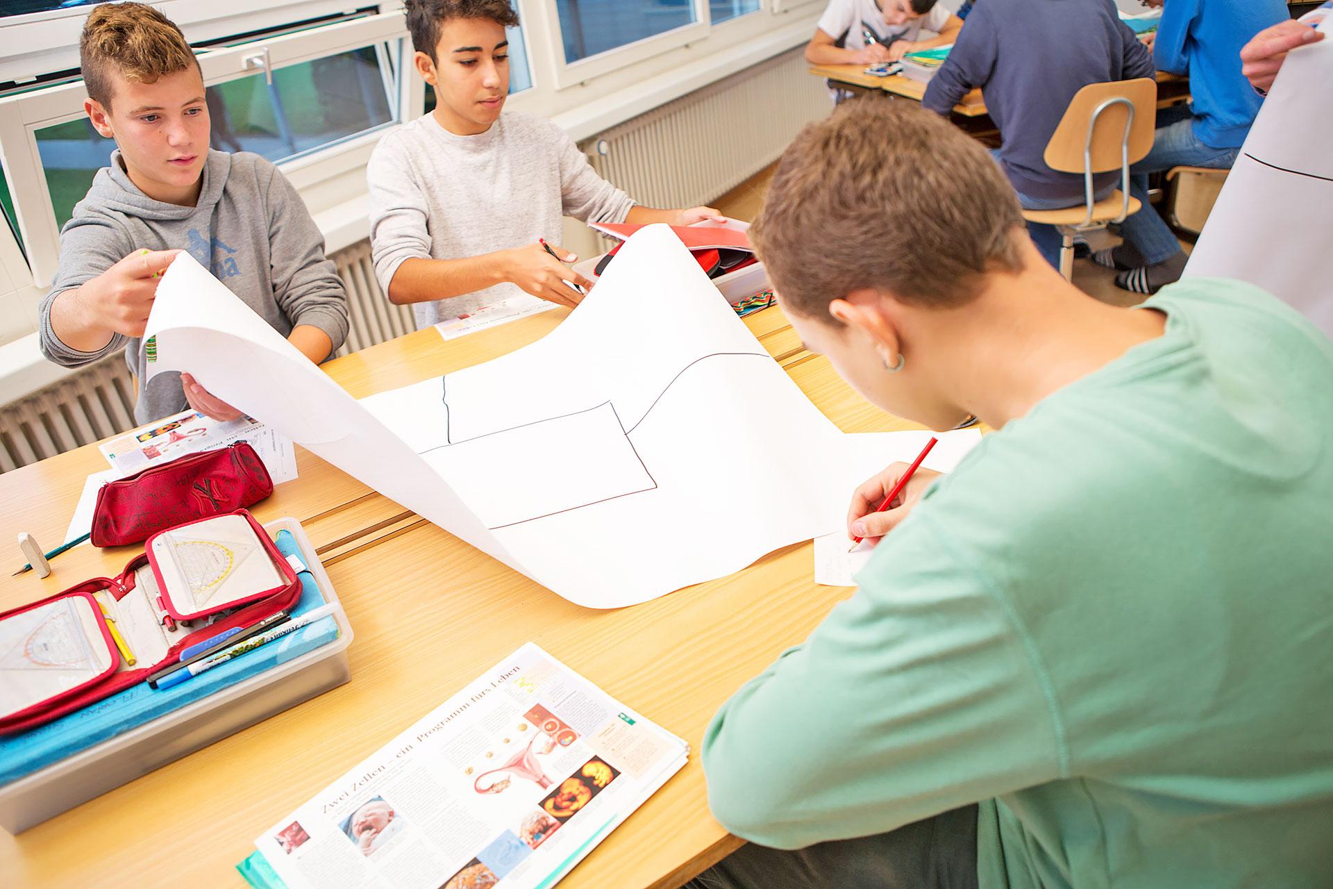 drei Schüler arbeiten an einem Placemat