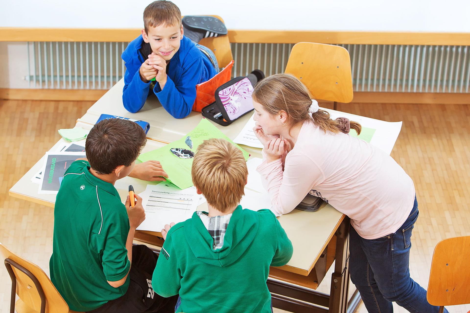 vier Schüler besprechen eine Tiervorstellung am Vierertisch