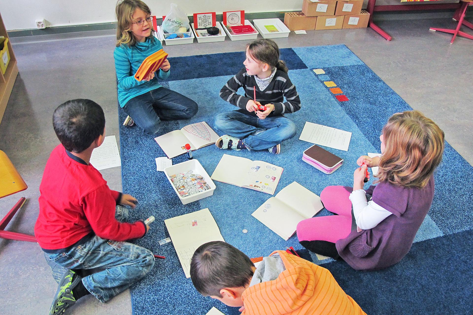 fünf Lernende sitzen auf einem Teppich im Schulzimmer und lösen Aufgaben