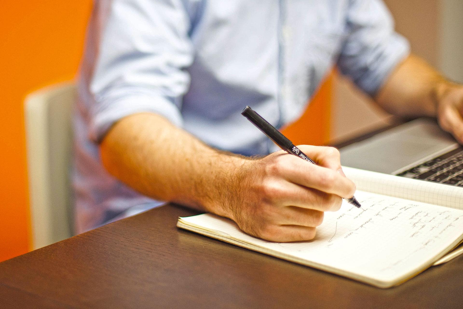 Mann macht sich handschriftliche Notizen in ein Heft