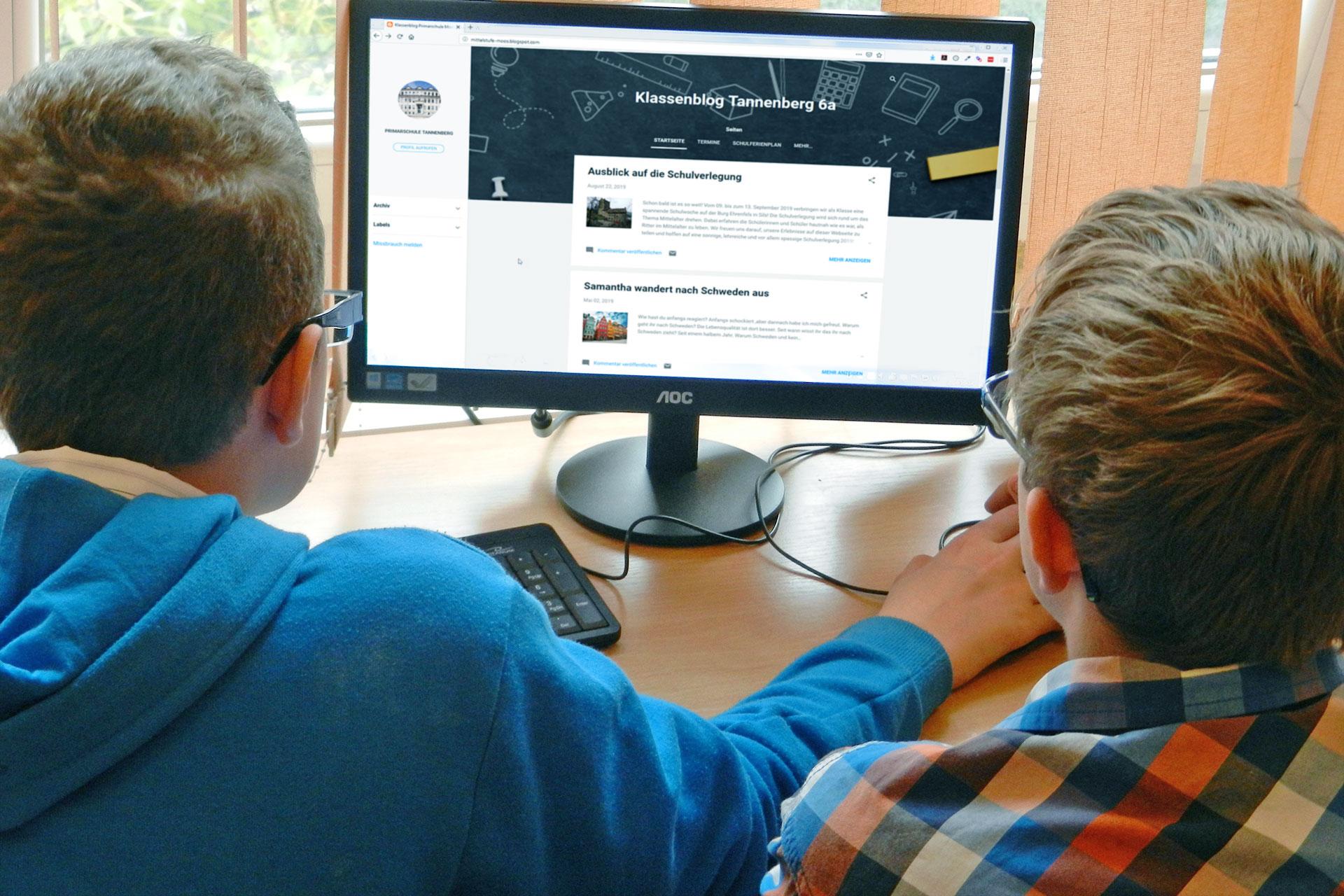 zwei Jungen arbeiten am Klassenblog auf einem Computer im Schulzimmer