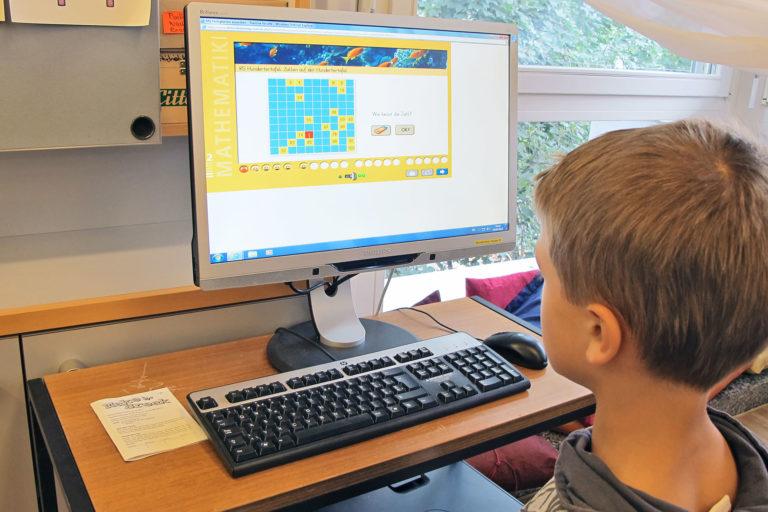 Junge löst am Computer Mathematikaufgaben