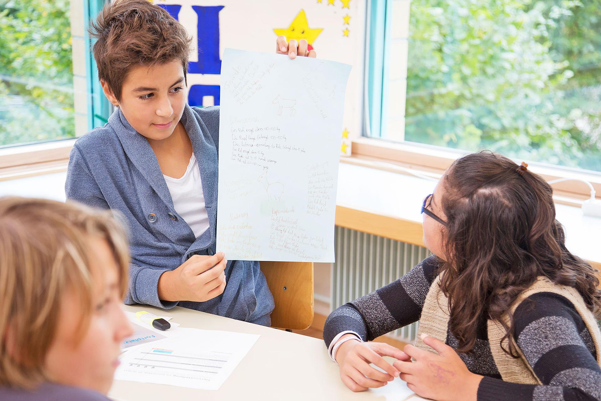 Schüler präsentiert einer Mitschülerin sein Plakat zur Tiervorstellung am Gruppentisch