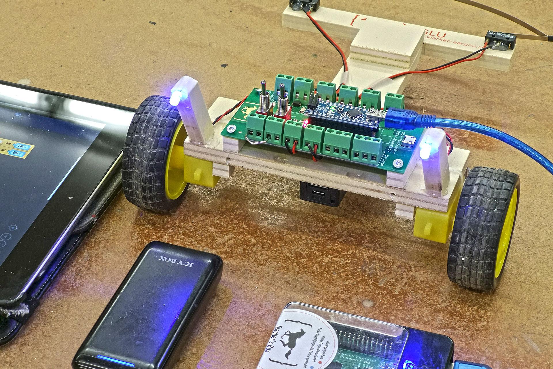 fertig gebautes selbstfahrendes Auto mit Tablet und Programmierungsbox