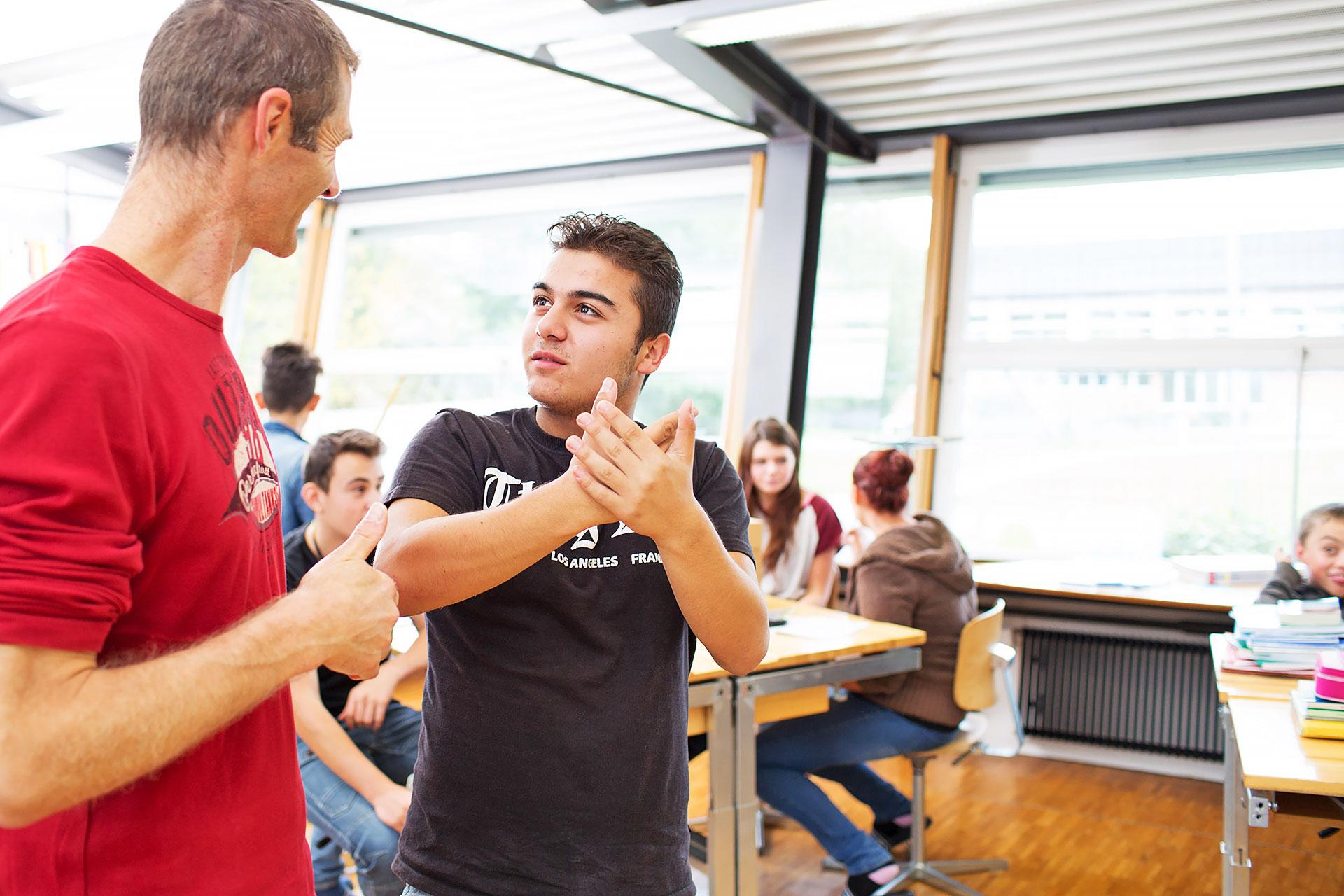Schüler im Gespräch mit dem Lehrer im Schulzimmer