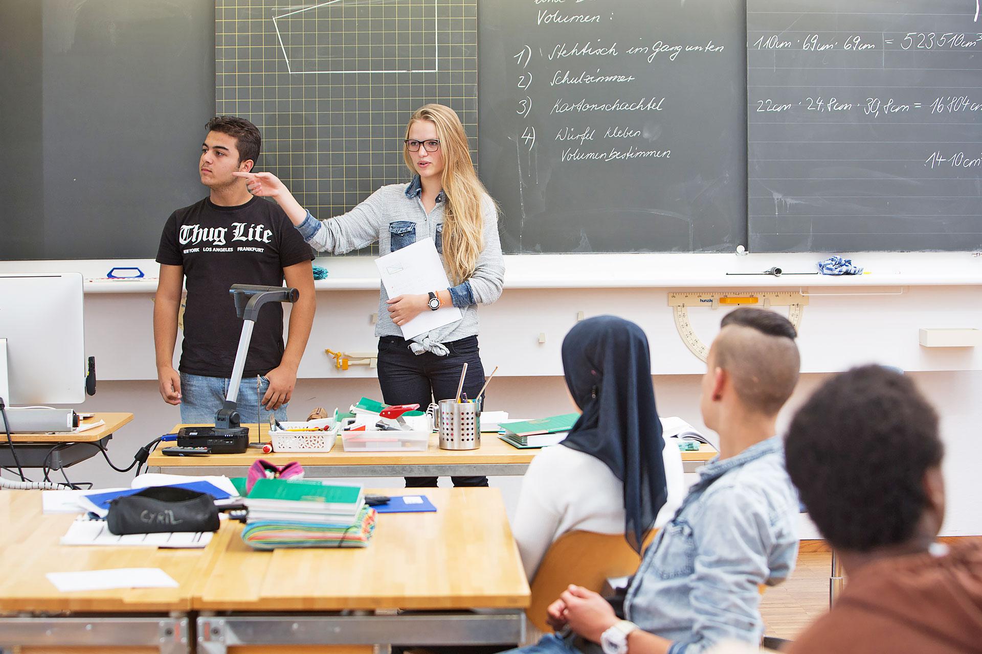 eine Schülerin und ein Schüler halten einen Vortrag vor der Klasse