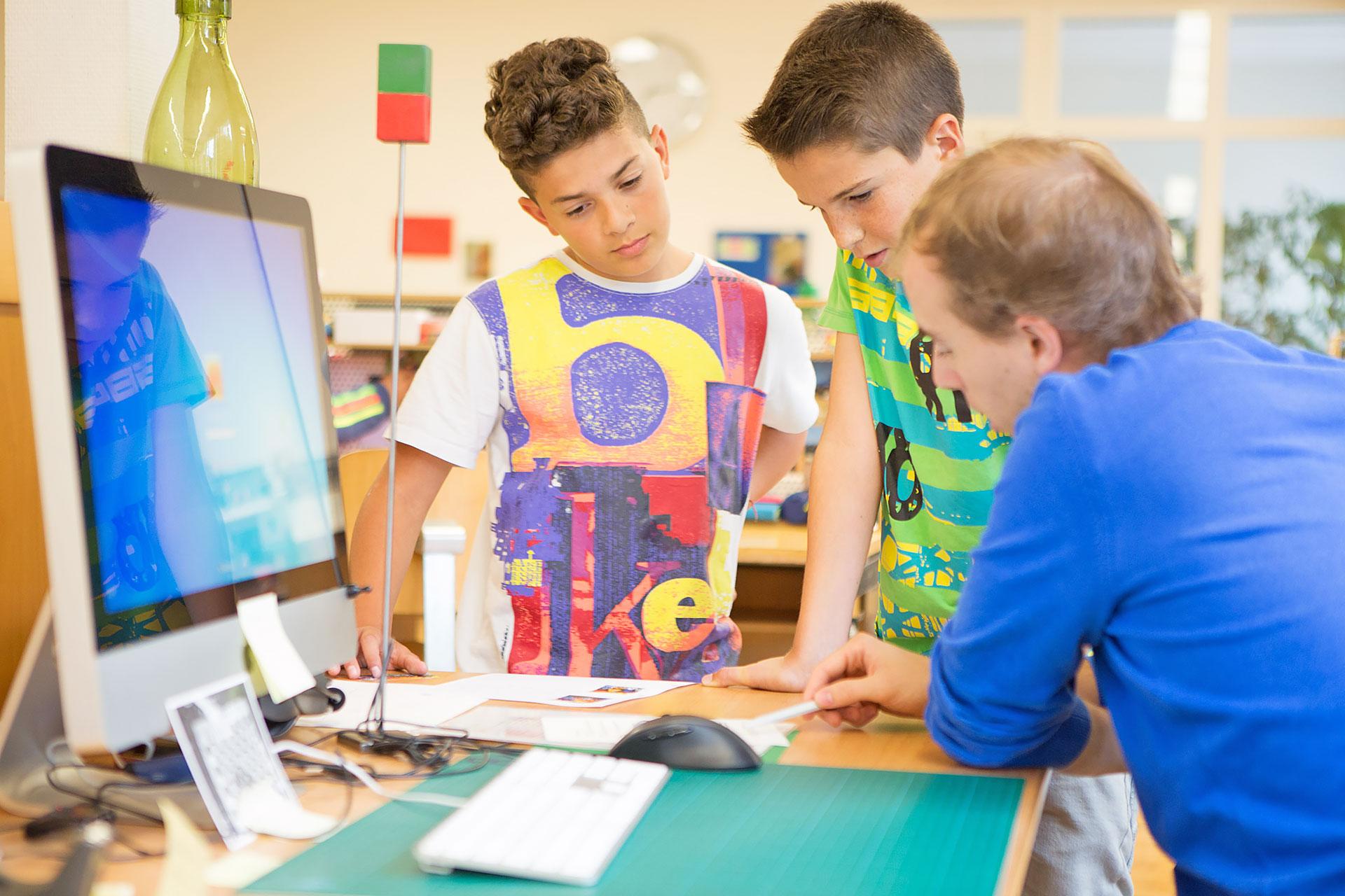 Lehrer erklärt zwei Schülern eine Aufgabe