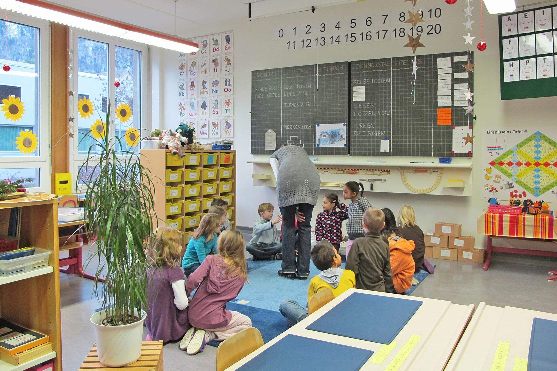 Schüler sitzen im Schulzimmer im Kreis auf dem Teppich