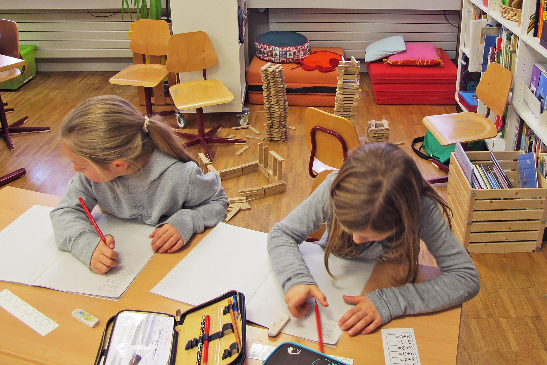 zwei Schülerinnen lösen Mathematikaufgaben, im Hintergrund stehen gestapelte Holztürme