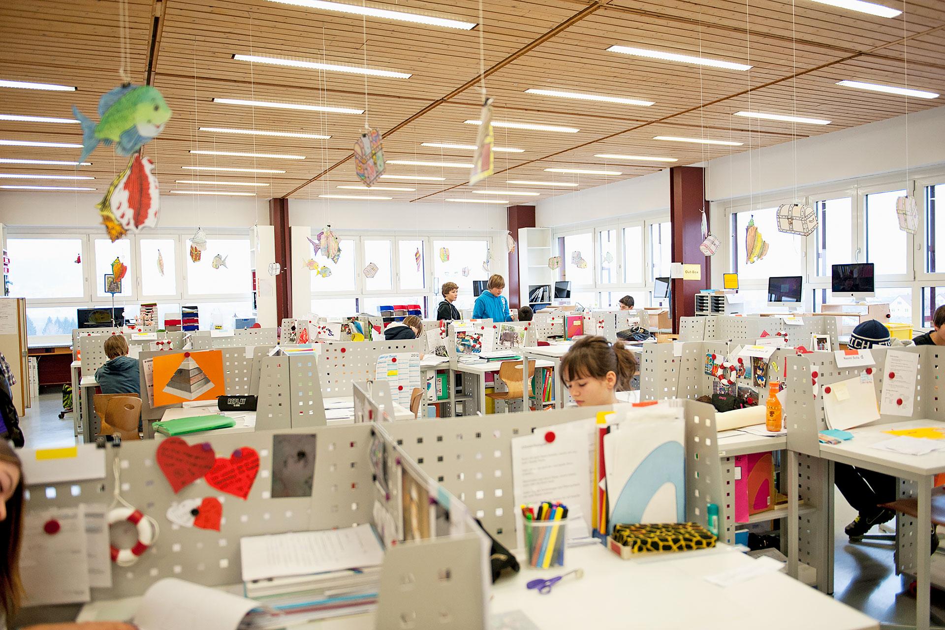 Blick in das als Lernlandschaft eingerichtete Schulzimmer mit persönlichen Arbeitsplätzen