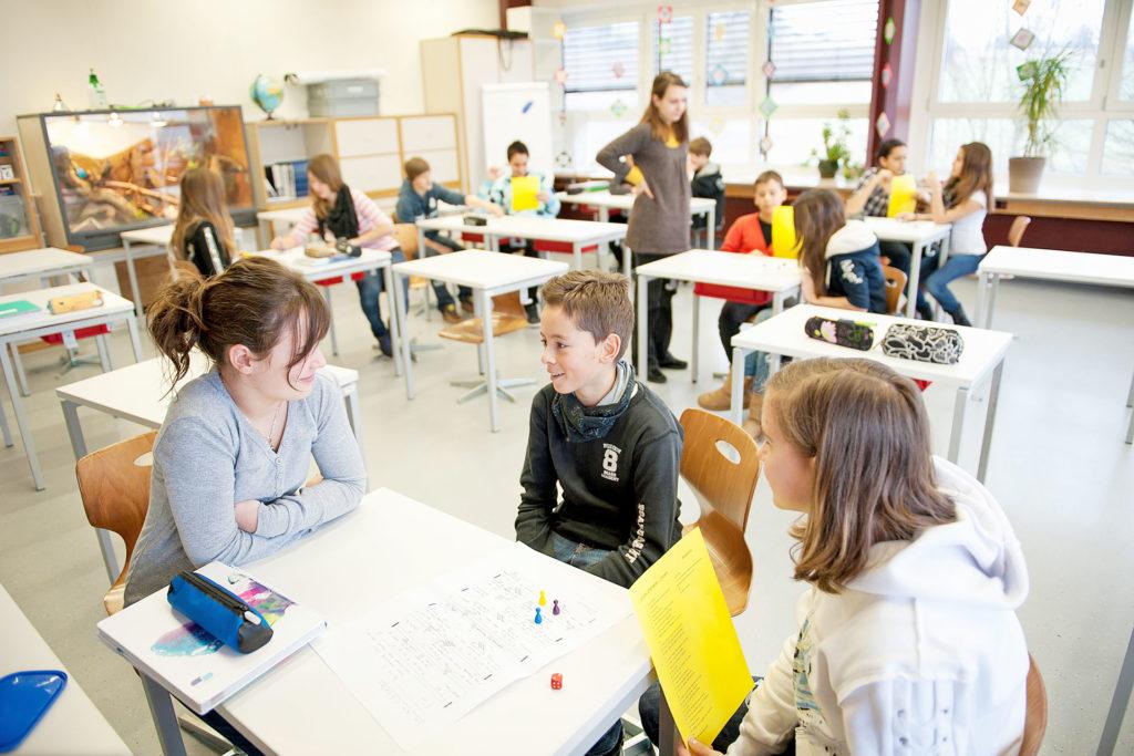 Lehrerin sitzt mit einem Schüler und einer Schülerin an einem Tisch