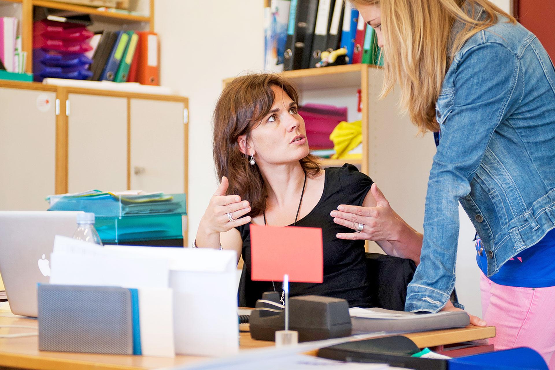 Lehrerin spricht mit einer Schülerin am Lehrerpult