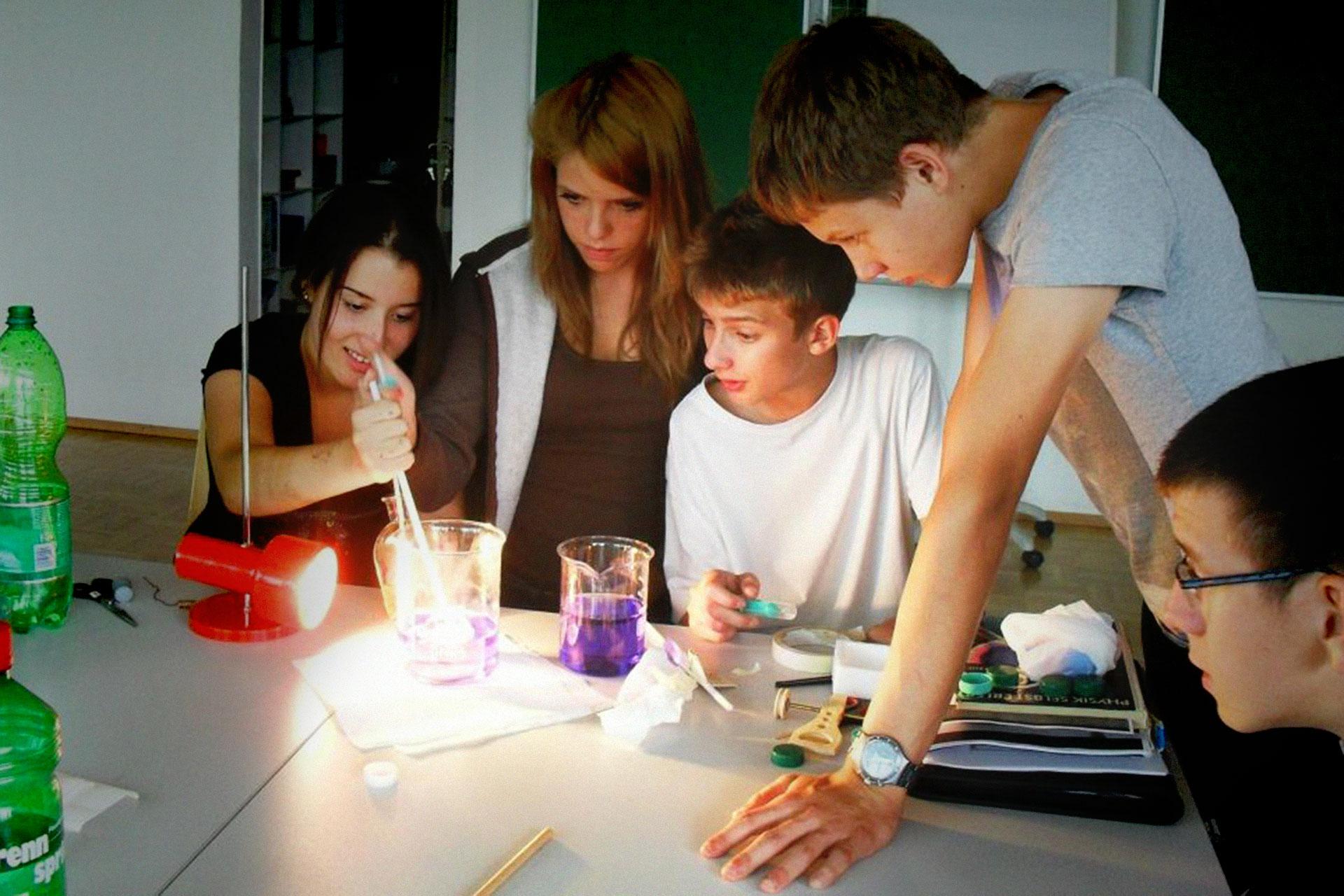 fünf Lernende führen ein Experiment durch