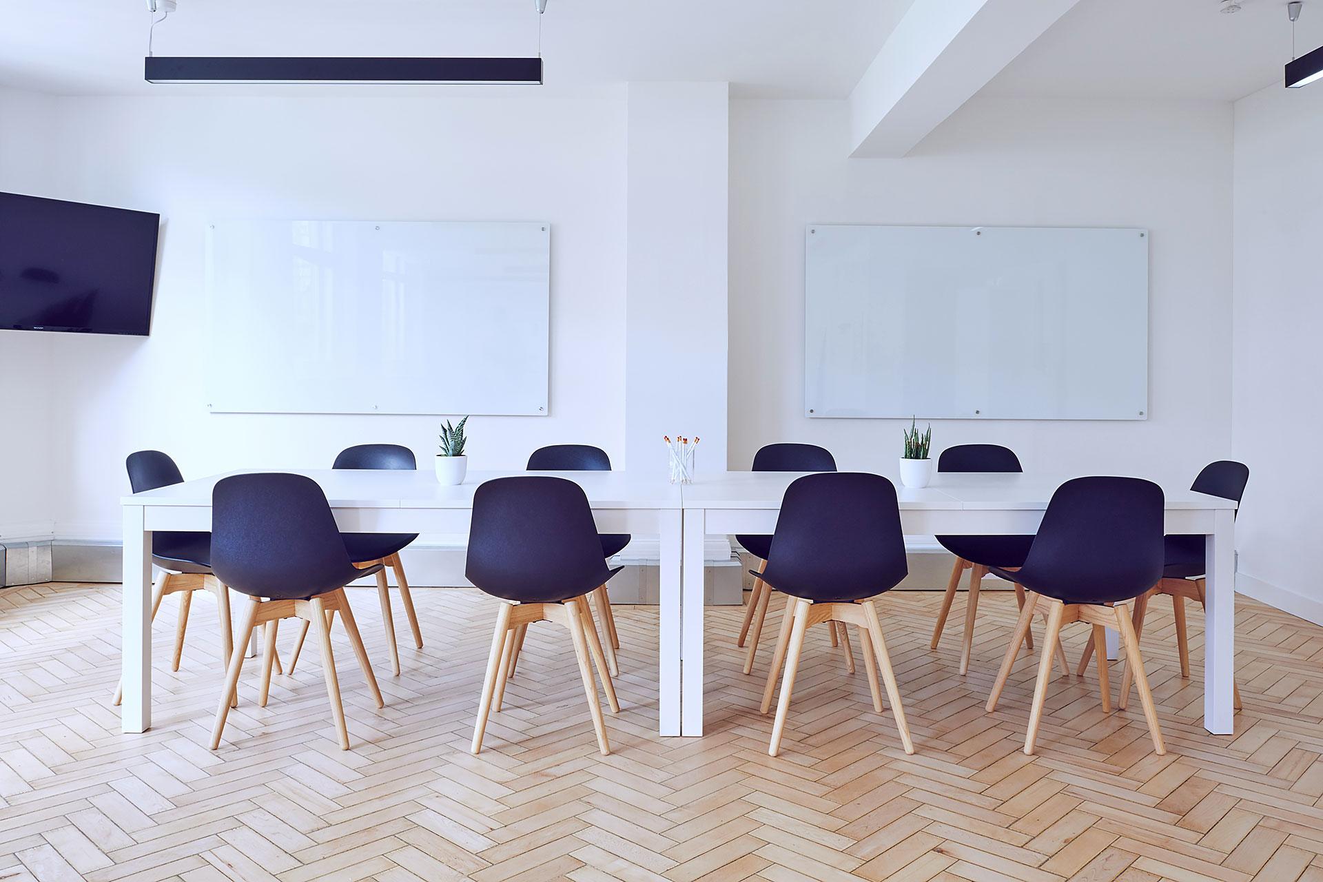Blick in ein Konferenzzimmer mit einem langen Tisch mit zehn Stühlen