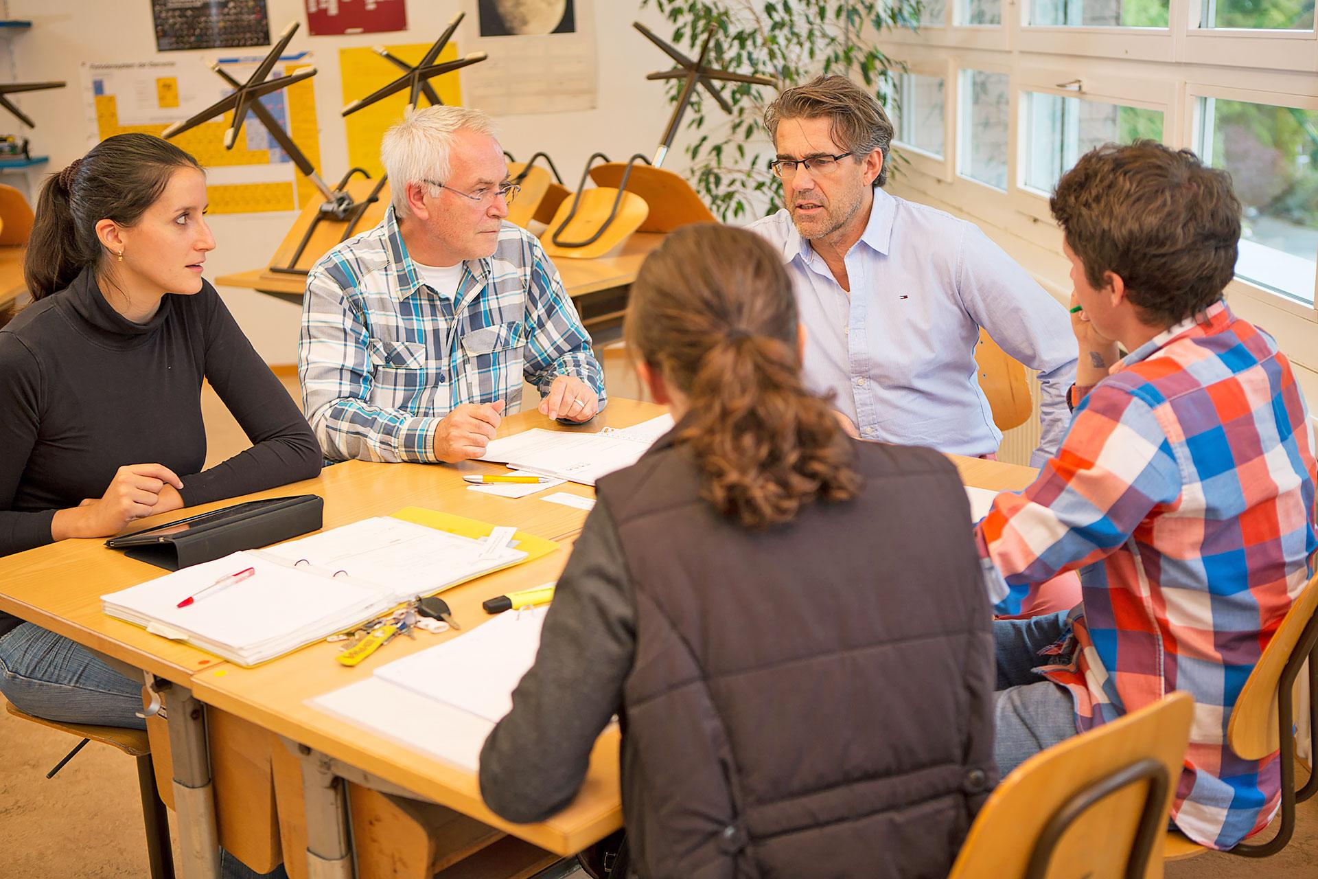 Fünf Personen während einer Besprechung in einem Schulzimmer