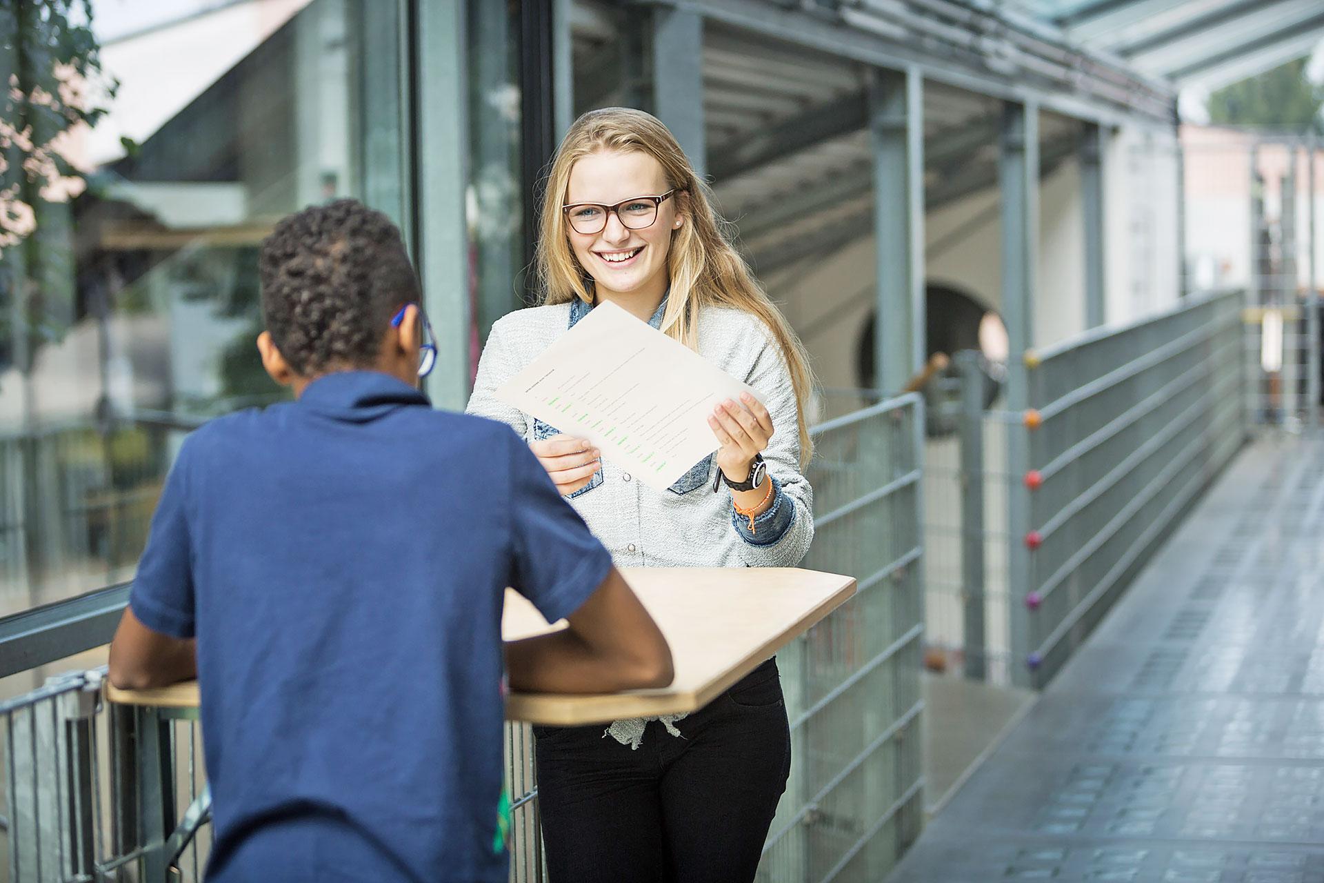 eine Schülerin und ein Schüler arbeiten in Partnerarbeit an einem Stehpult auf dem Korridor