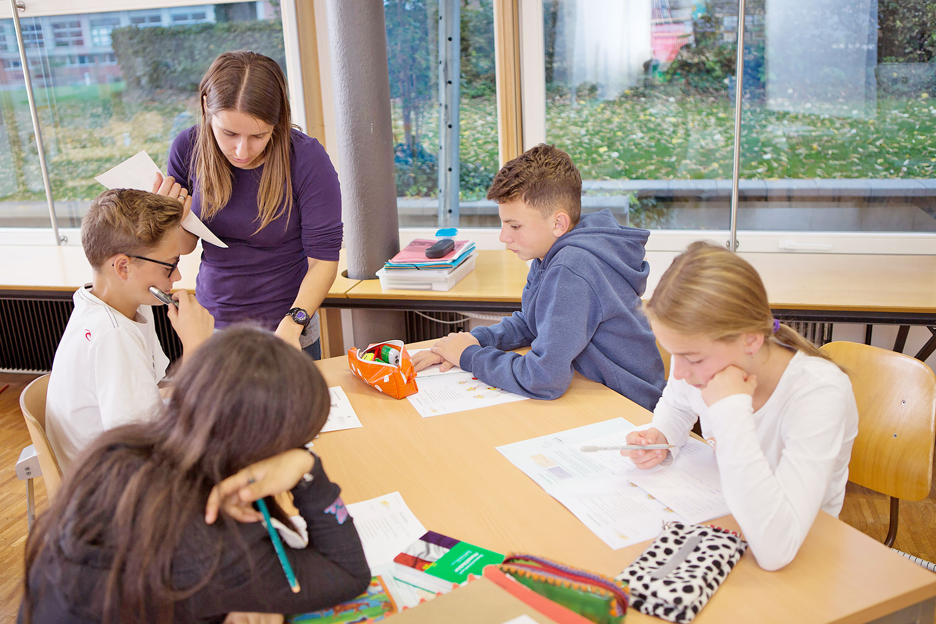 Lehrerin gibt einem Schüler ein Feedback am Gruppentisch
