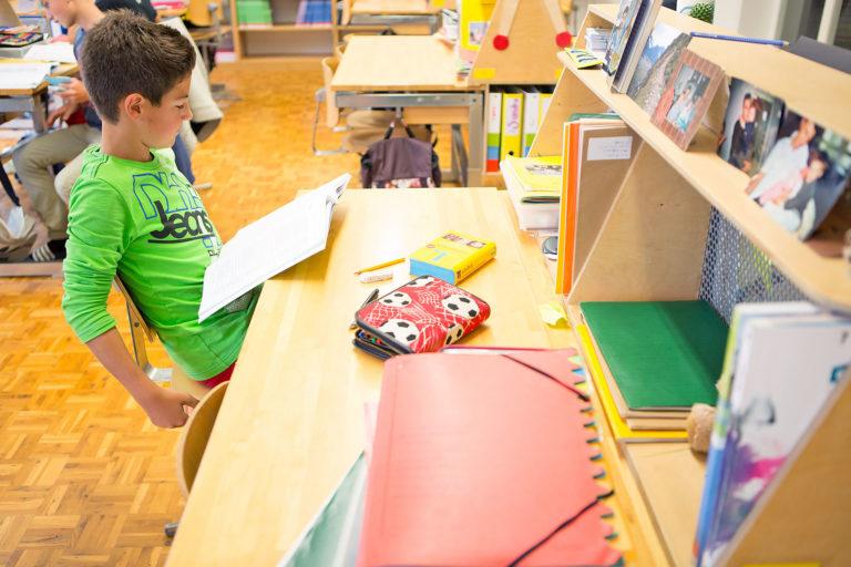 ein Schüler liest an seinem persönlichen Arbeitsplatz in der Lernlandschaft