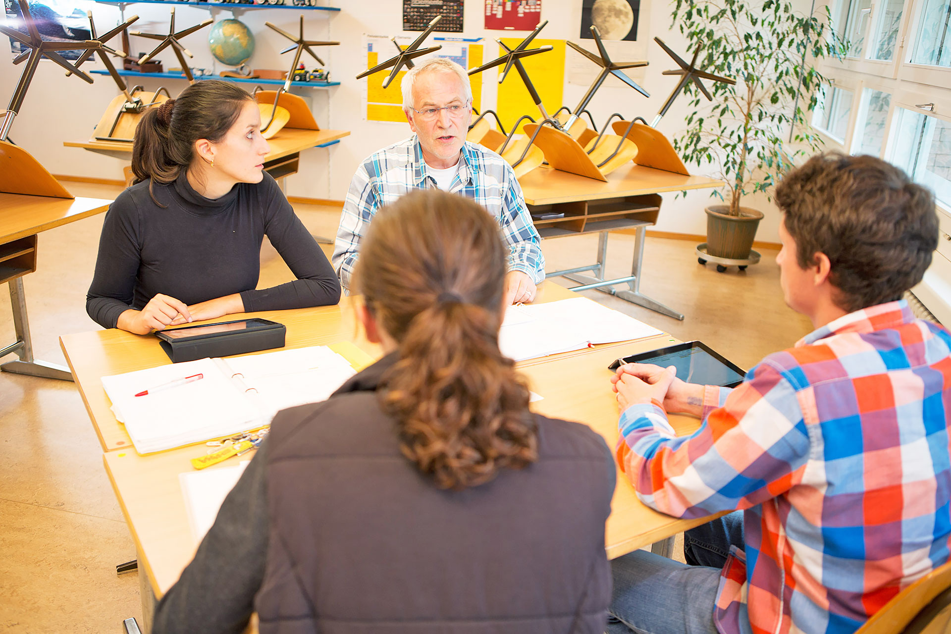 Vier Personen während einer Besprechung in einem Schulzimmer