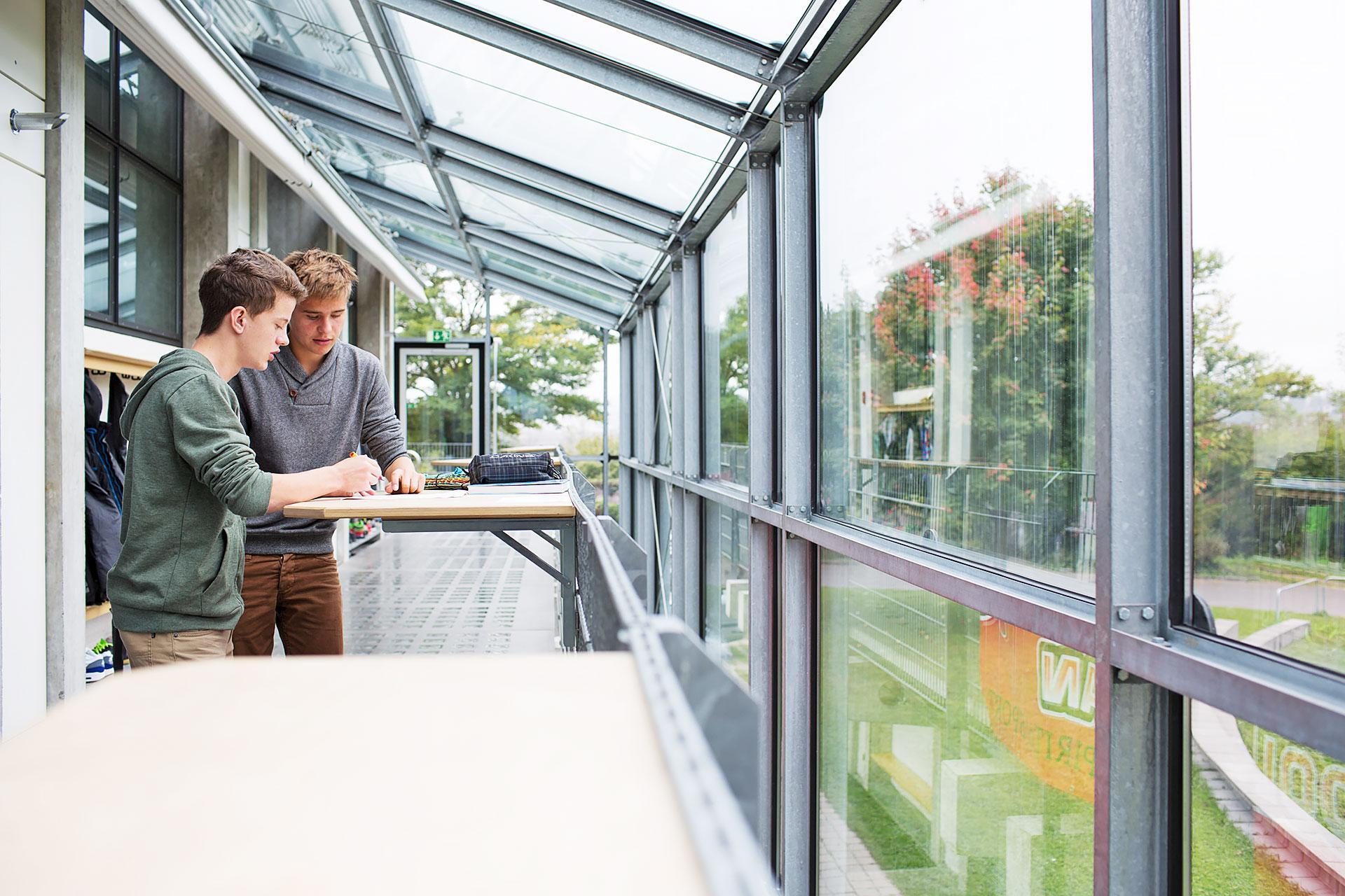 zwei Schüler arbeiten kooperativ an einer Aufgabe an einem Stehpult