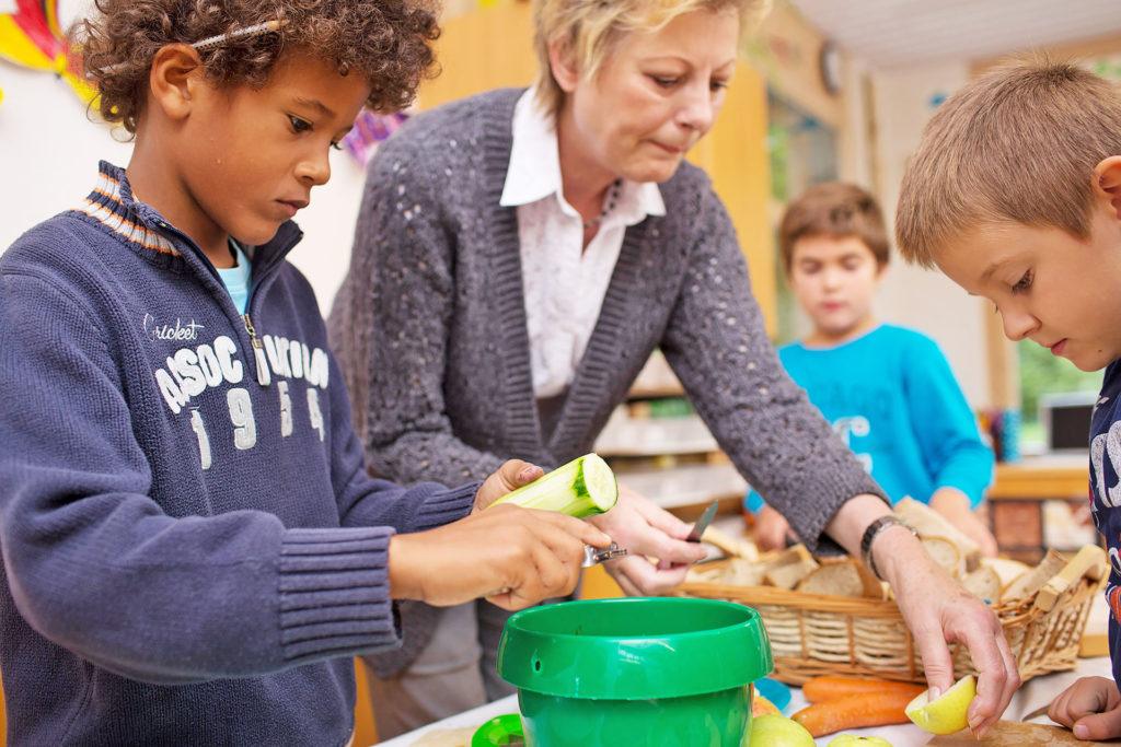 ein Schüler schält eine Gurke im Kochunterricht