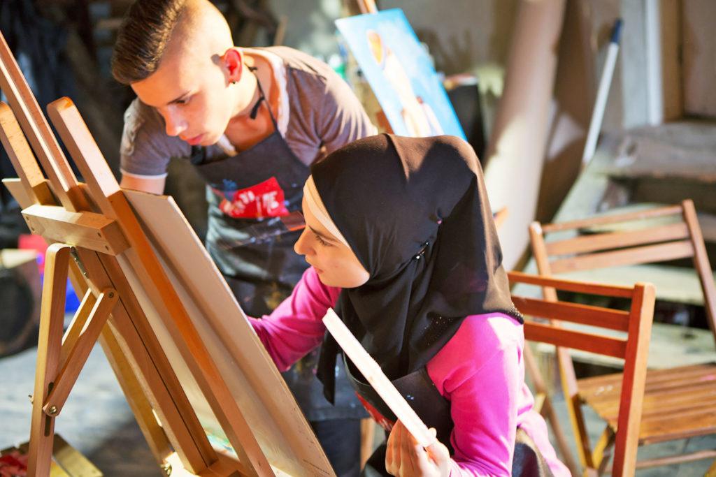 Mädchen und Junge arbeiten an einem Bild im Kunstatelier