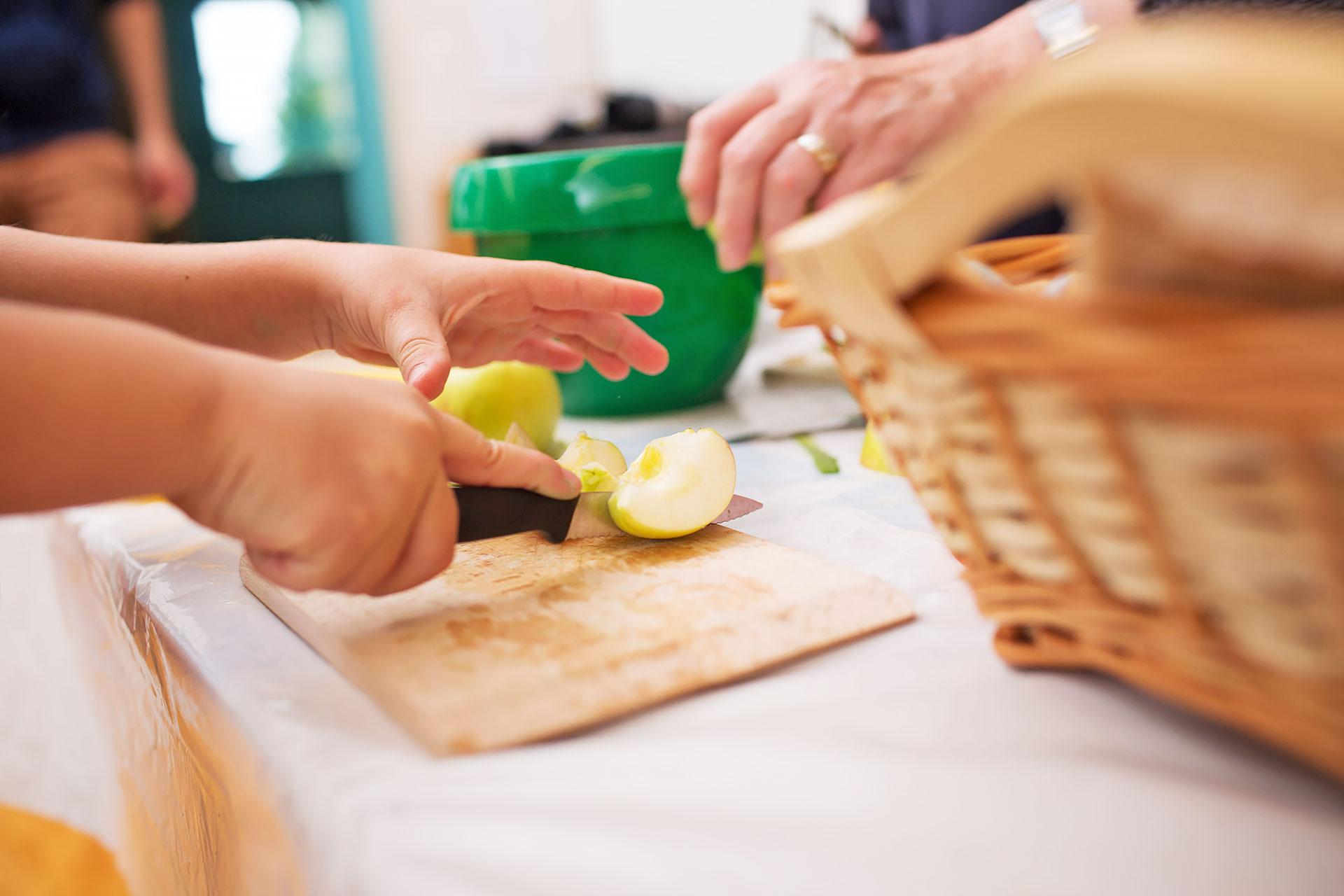 Kind schneidet einen Apfel